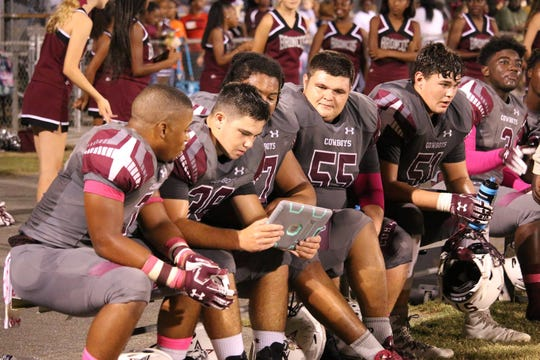Madison County players, including center Zac Coe (55) look at film of a play.