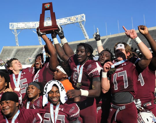 Travis Jay (8) and Patrick Hampton (6) hold the trophy aloft as Madison County's football team celebrates winning a Class 1A state championship game with a 48-6 win over Baker on Thursday at Camping World Stadium in Orlando.