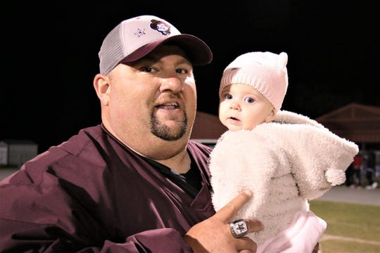 Madison County head football coach Mike Coe with 7-month-old daughter Madison, who is named after the city in which they live.