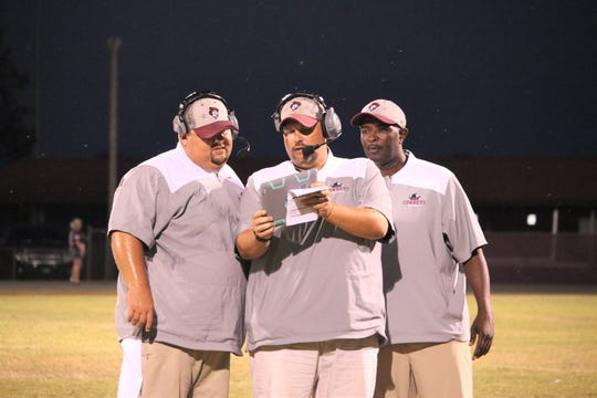 Madison County assistant coach Jim Ertzberger shows footage to head coach Mike Coe and assistant Morris Bell (right) during a recent game.
