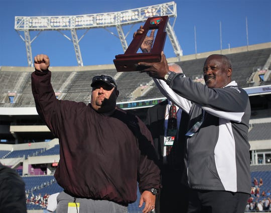 Madison County head football coach Mike Coe is awarded the Class 1A state championship trophy following a 48-6 win over Baker on Thursday at Orlando's Camping World Stadium.