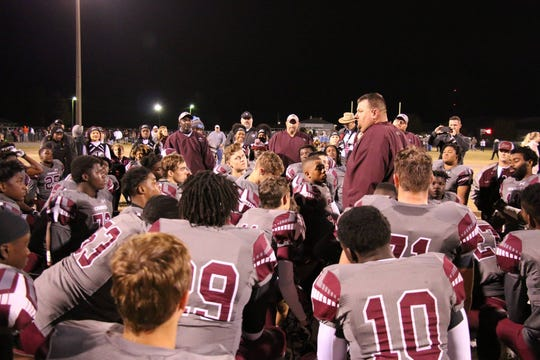 Madison County head coach Mike Coe talks to his team after a football game.