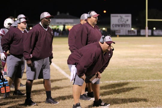 Madison County head coach Mike Coe watches his team with his assistant coaches.