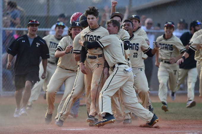 Jaiden Salerno (center) of Treasure Coast High School is congratulated by his team mates after scoring the winning run in the bottom of the 10th inning during their home game against Vero Beach High School on Friday, March 2, 2018, in Port St. Lucie. Treasure Coast won 2-1 over Vero Beach in their district game.