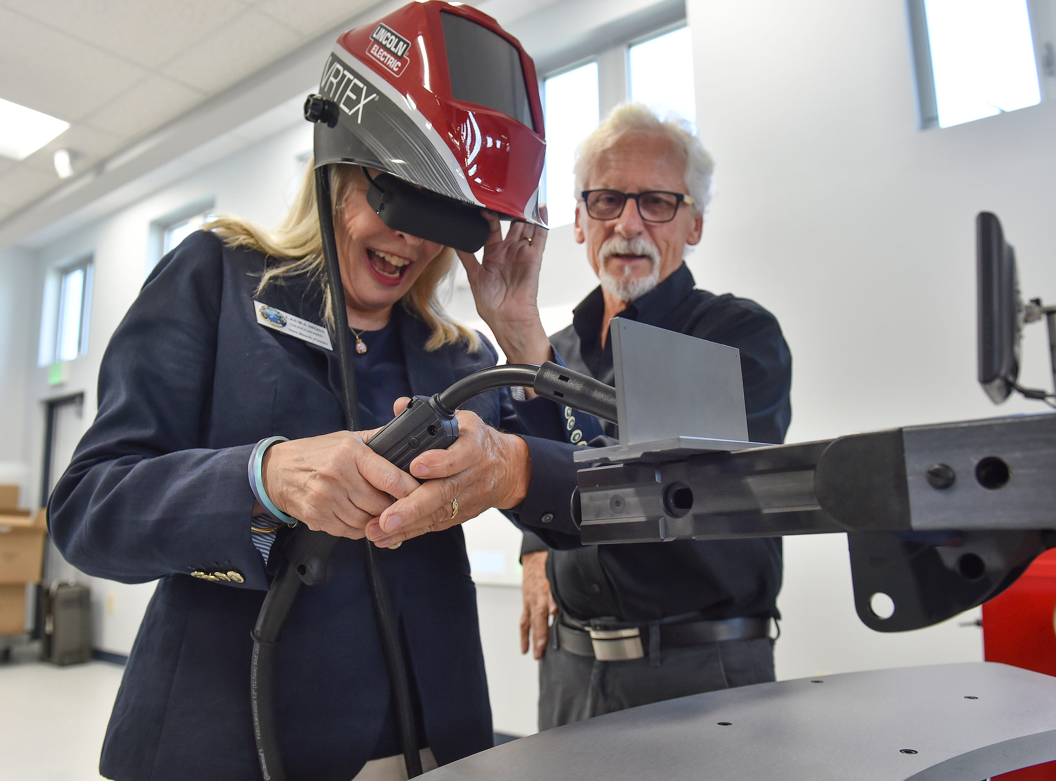 """Laura Moss, councilwoman with the City of Vero Beach, tries out a virtual reality welding trainer with the help of Michael Klee, representative for Lincoln Electric of Cleveland, Ohio, while touring the campus of Treasure Coast Technical College during the school's ribbon cutting ceremony Thursday, August, 9, 2018, in Indian River County. """"I really did it, isn't that great,"""" Moss said afterword. """"I am so impressed with this facility, it really will be a wonderful asset for the community, it was so much fun to try the virtual welding myself."""""""