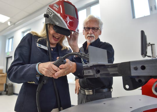 "Laura Moss, councilwoman with the City of Vero Beach, tries out a virtual reality welding trainer with the help of Michael Klee, representative for Lincoln Electric of Cleveland, Ohio, while touring the campus of Treasure Coast Technical College during the school's ribbon cutting ceremony Thursday, August, 9, 2018, in Indian River County. ""I really did it, isn't that great,"" Moss said afterword. ""I am so impressed with this facility, it really will be a wonderful asset for the community, it was so much fun to try the virtual welding myself."""