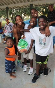 The Noble family children are all smiles as they receive their turkey Nov. 20 at the Victor Hart Park Complex.