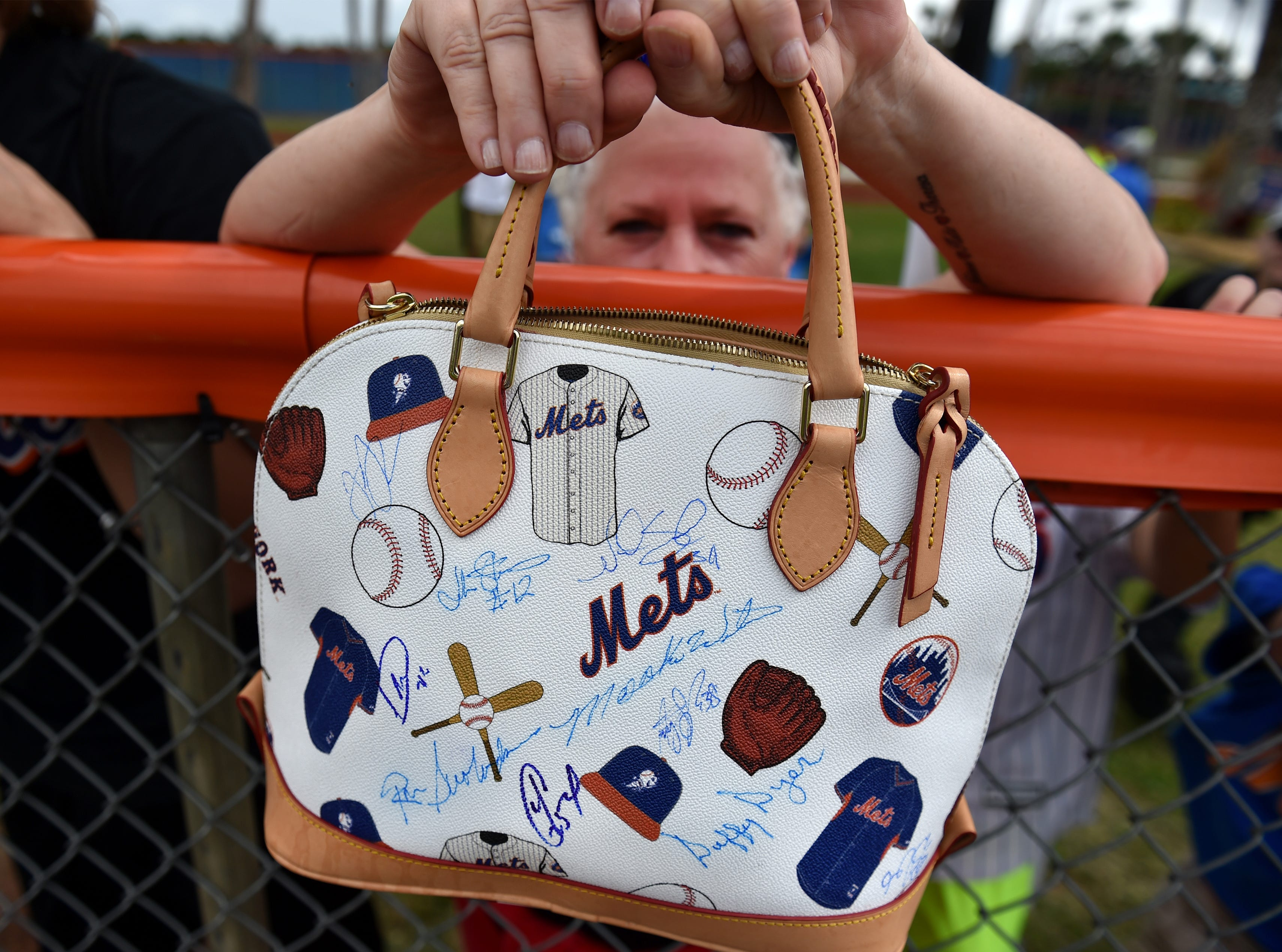 """Gigi Bowman, of Port St. Lucie, waits for autographs on her purse as the New York Mets pitchers and catchers start to walk by after finishing their workouts on Wednesday, Feb. 14, 2016 at First Data Field in Port St. Lucie. """"This is like my dream,"""" Bowman said."""