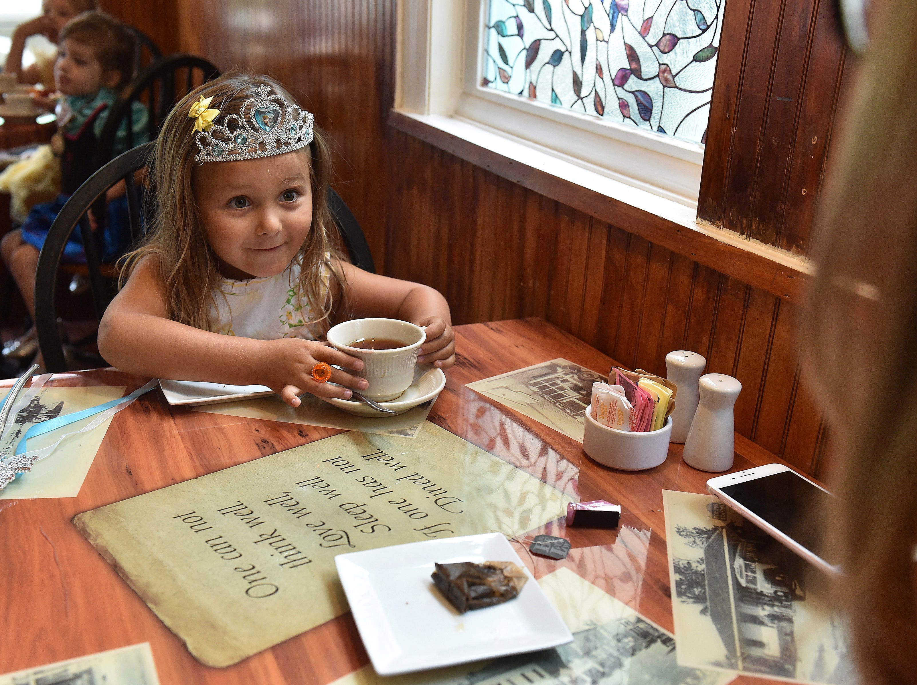 """Attired in a combination of Disney princesses Belle, of Beauty and the Beast, and Elsa, from Frozen, Mia Raaz, 4, of Jensen Beach, prepares to sample a tea prepared by her mother Lauren Raaz (right) during a Tea for Kids party at Banyon 320 Kitchen and Bar, at 320 SE Denver Avenue on Tuesday, July 24, 2018, in Stuart. """"I think it's super cute, and fun for the kids, she was super excited to come,"""" Lauren Raaz said. """"She loves princesses and tea parties, and anything girly related."""" More than 25 children dressed as knights, princesses, pirates and other characters, along with their parents, grandparents or nannies were treated to tea, sandwiches, and fruits during the free event. """"When I opened here in December, I really wanted to create a place where families can come for fun activities that are free,"""" said Rachel Pias, owner and chef at Banyon 320. """"We usually try to do something bi-monthly whether it's a kids cooking activity or tea party…whatever we can think of that's new and fun and keeps the activities exciting."""""""