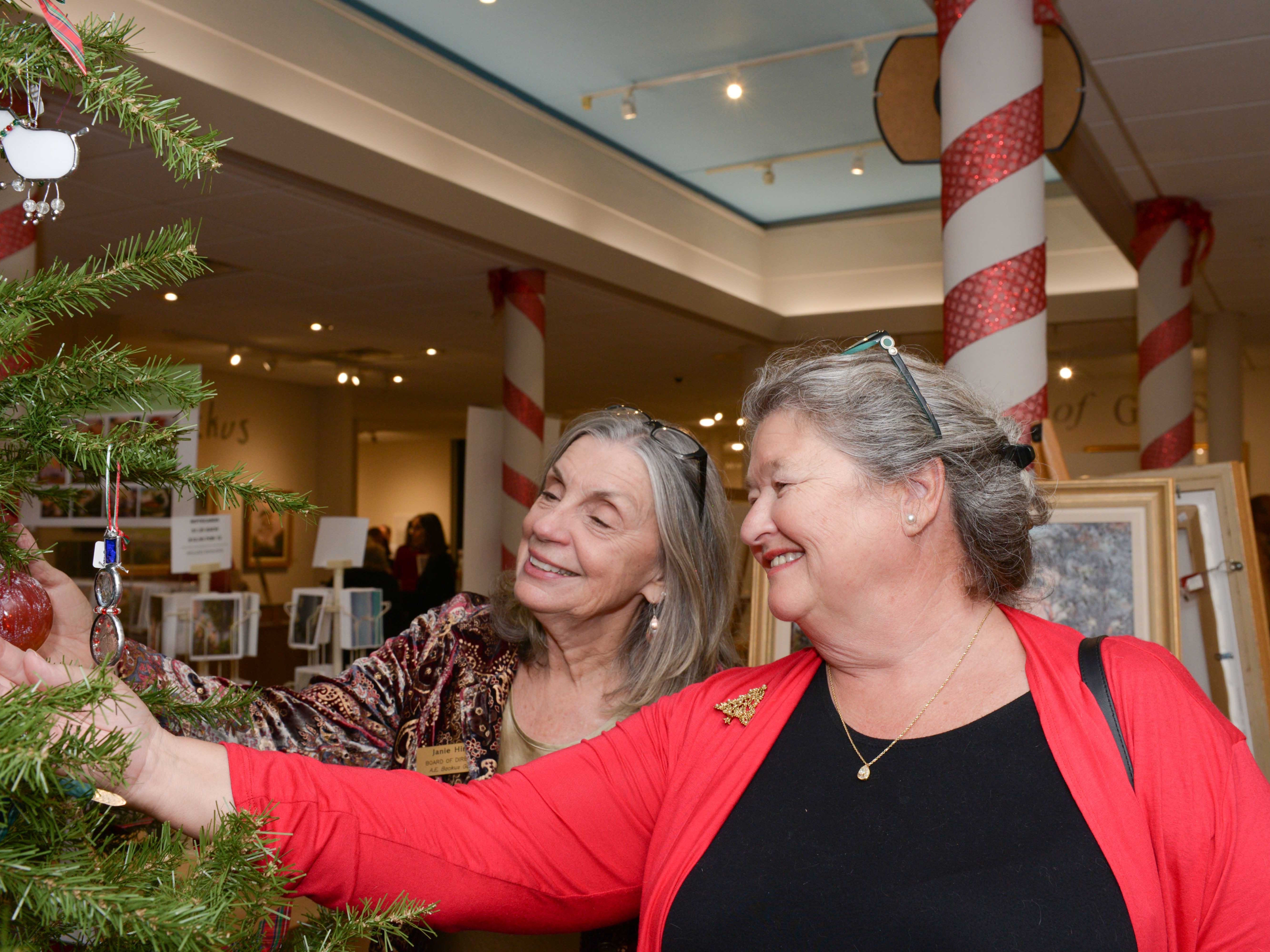 Board President Janie Hinkle, left, and Terry Shafer look at some Christmas tree ornaments at the A.E. Backus Museum in Fort Pierce.