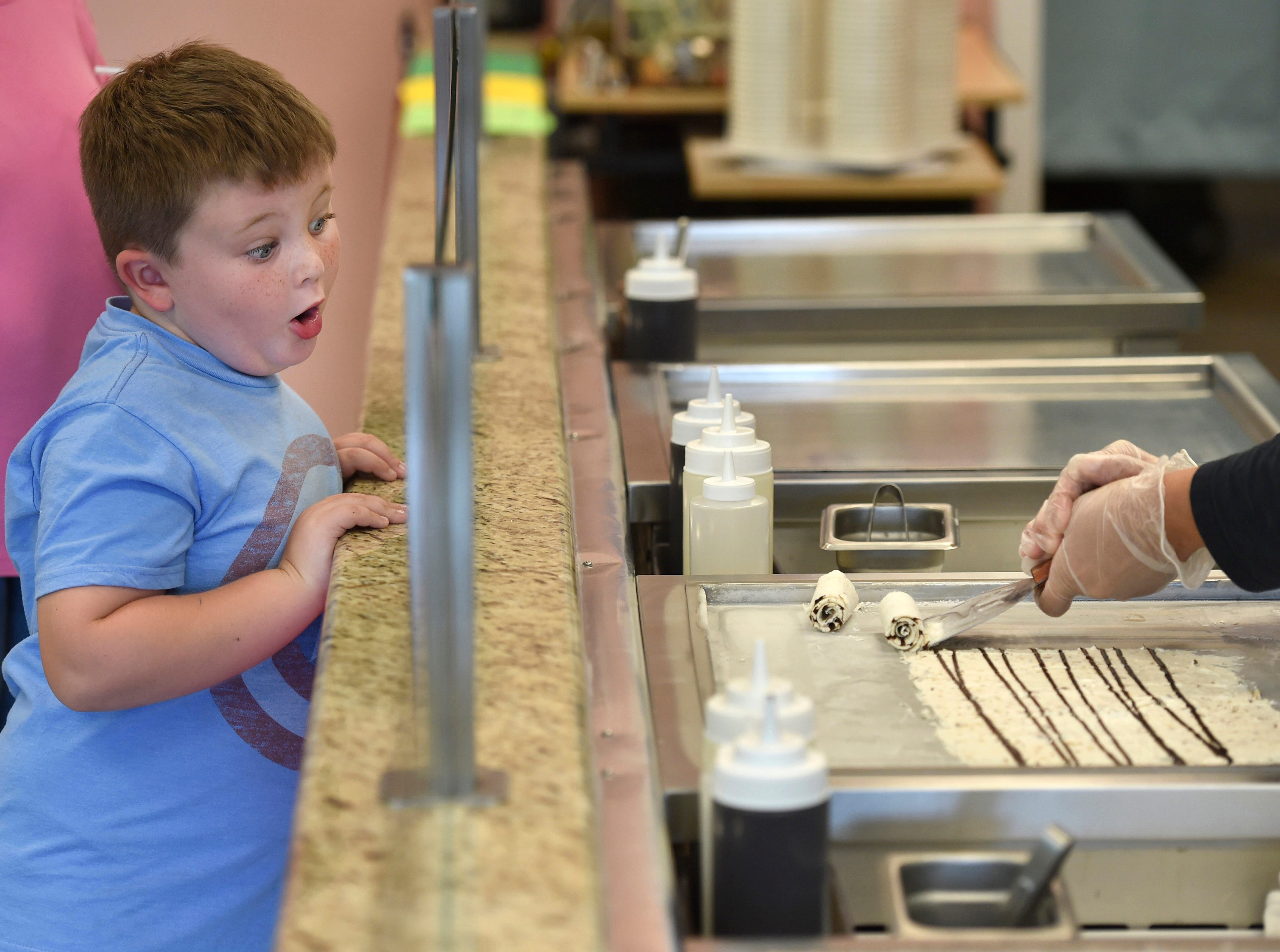 Malcolm Beauchamp, 5, of Vero Beach, watches the hands of Yasmin Falix, an employee of Steel N Roll, Rolling Ice Cream & More, as she makes an order for another customer. Malcolm thought the best part of the ice cream making process was watching the ice cream being rolled. Malcolm was being treated to a serving of ice cream by his grandmother Linda MacMenigall (far left).