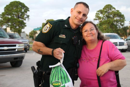 Indian River County Sheriff's Deputy Anthony Muraca helps Jean Smoak to her car with a turkey in hand on Nov. 20 at the Victor Hart Park Complex.