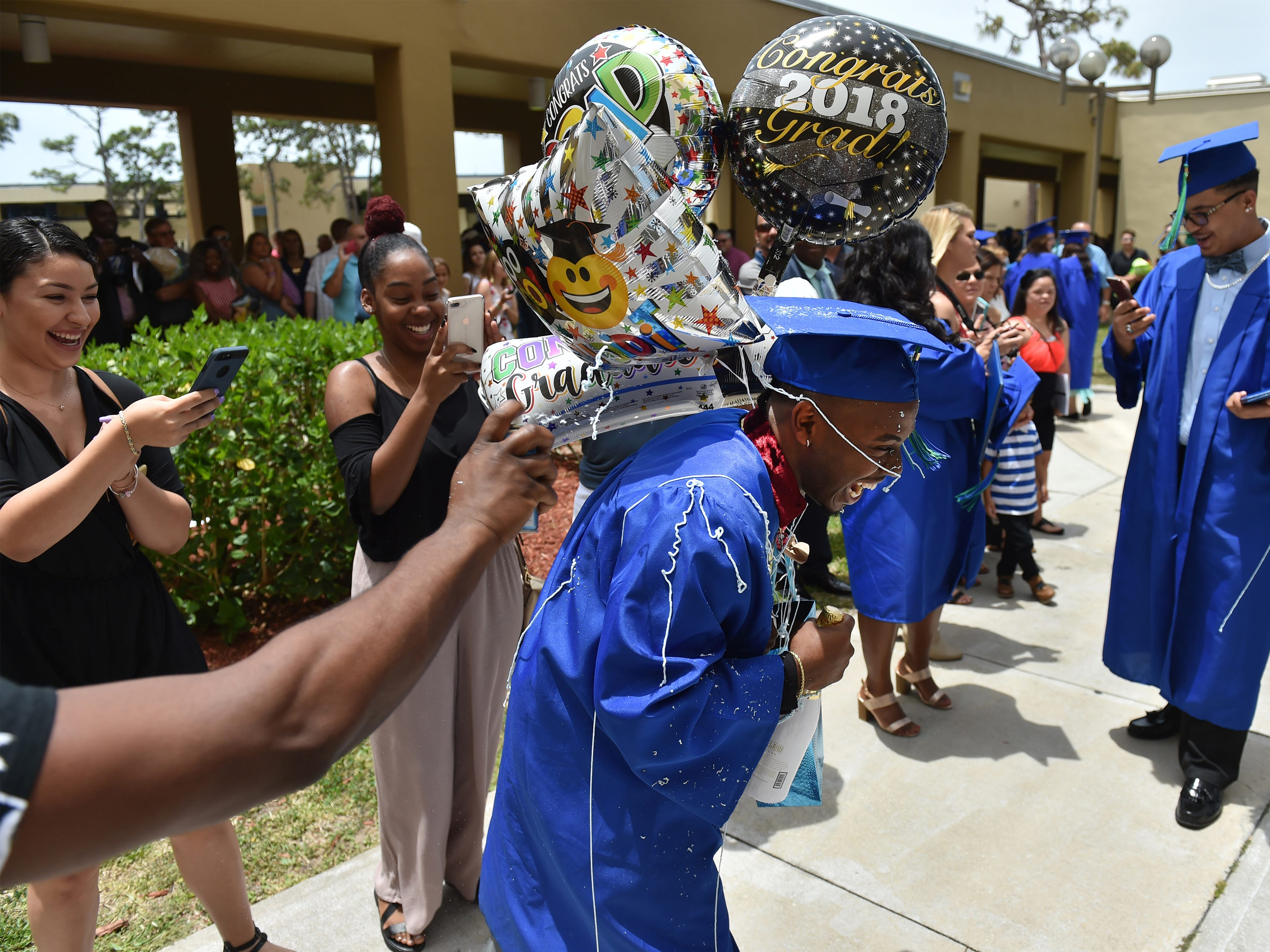 """Damion Dixon, 21, of Palm Bay, gets sprayed with silly string celebrating with family after graduating with an AA degree outside the King Center after the first of two Eastern Florida State College commencement ceremonies on Thursday, May 10, 2018, in Melbourne. """"It's a beautiful feeling, beautiful feeling, it's great"""" Dixon said."""