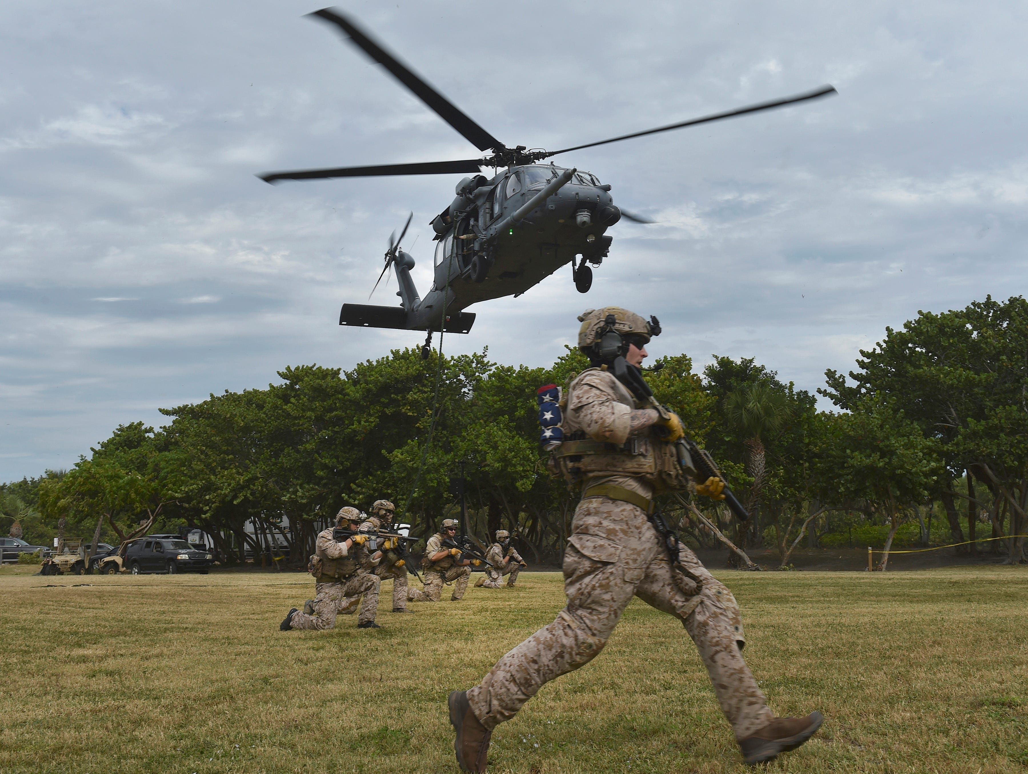 U.S. Navy SEALs stage onto the grounds of Pepper Park Beachside after rappelling from a Sikorsky HH-60 Pave Hawk Helicopter during practice for their SEAL tactical demonstration Friday, Nov. 2, 2018, in preparation for the National Navy UDT-SEAL Museum's 33rd annual Muster and Music Festival Saturday, Nov. 3, in Fort Pierce.
