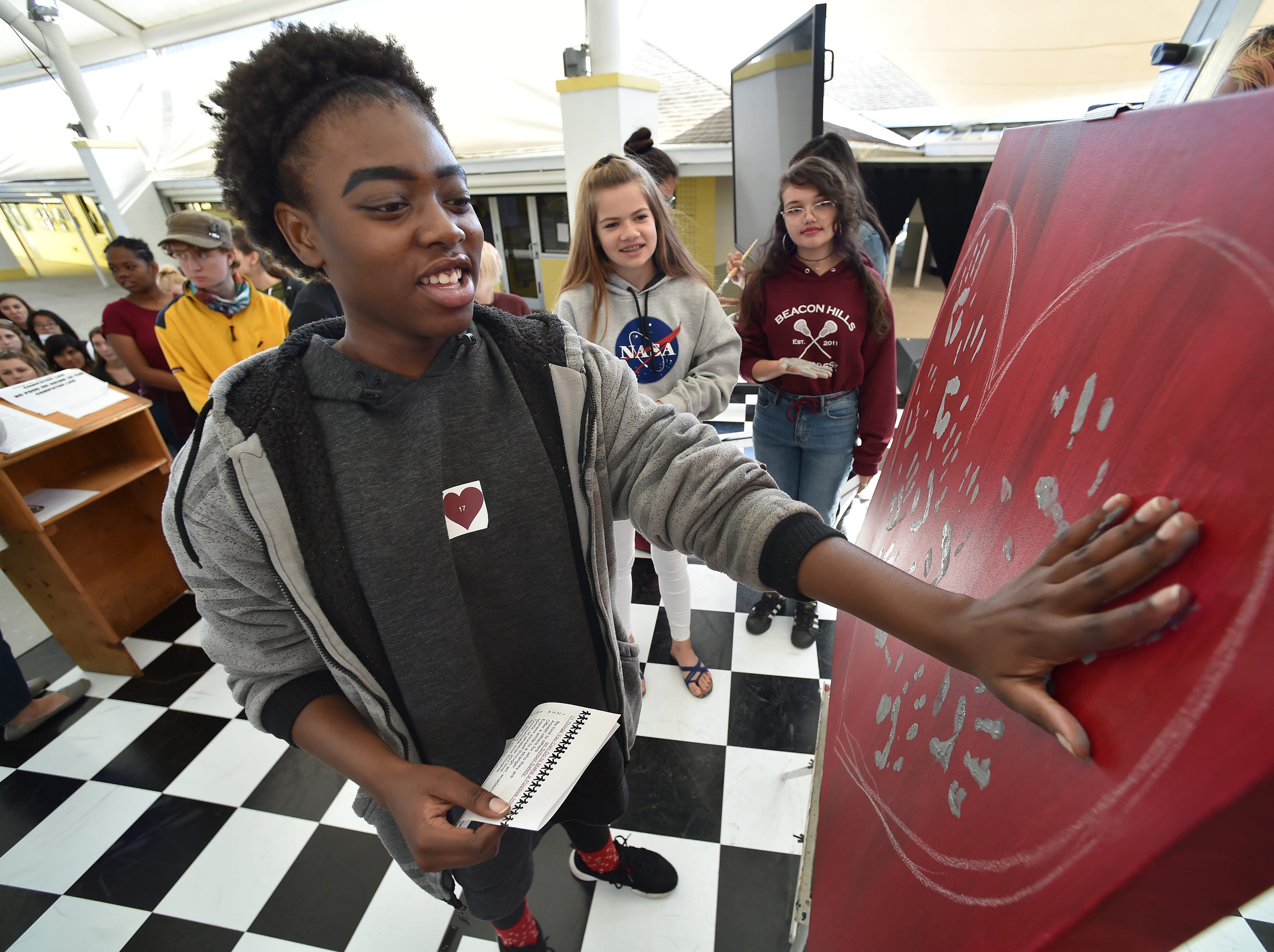 """Sarah Bathelemy, 15, a sophomore at Indian River Charter High School, adds her handprint to a canvas during the school's observance of National Walkout Day, in which the school chose to have a school-wide Walk In to honor the 17 students and teachers killed in the Parkland shooting. More than 650 students and faculty participated in the ceremony under the dome of the school's courtyard on Wednesday, March 14, 2018 in Vero Beach. """"Amazing, I feel delighted and lifted up,"""" Sarah said after adding her handprint to the canvas, to later be presented to Stoneman Douglas High School in Parkland."""