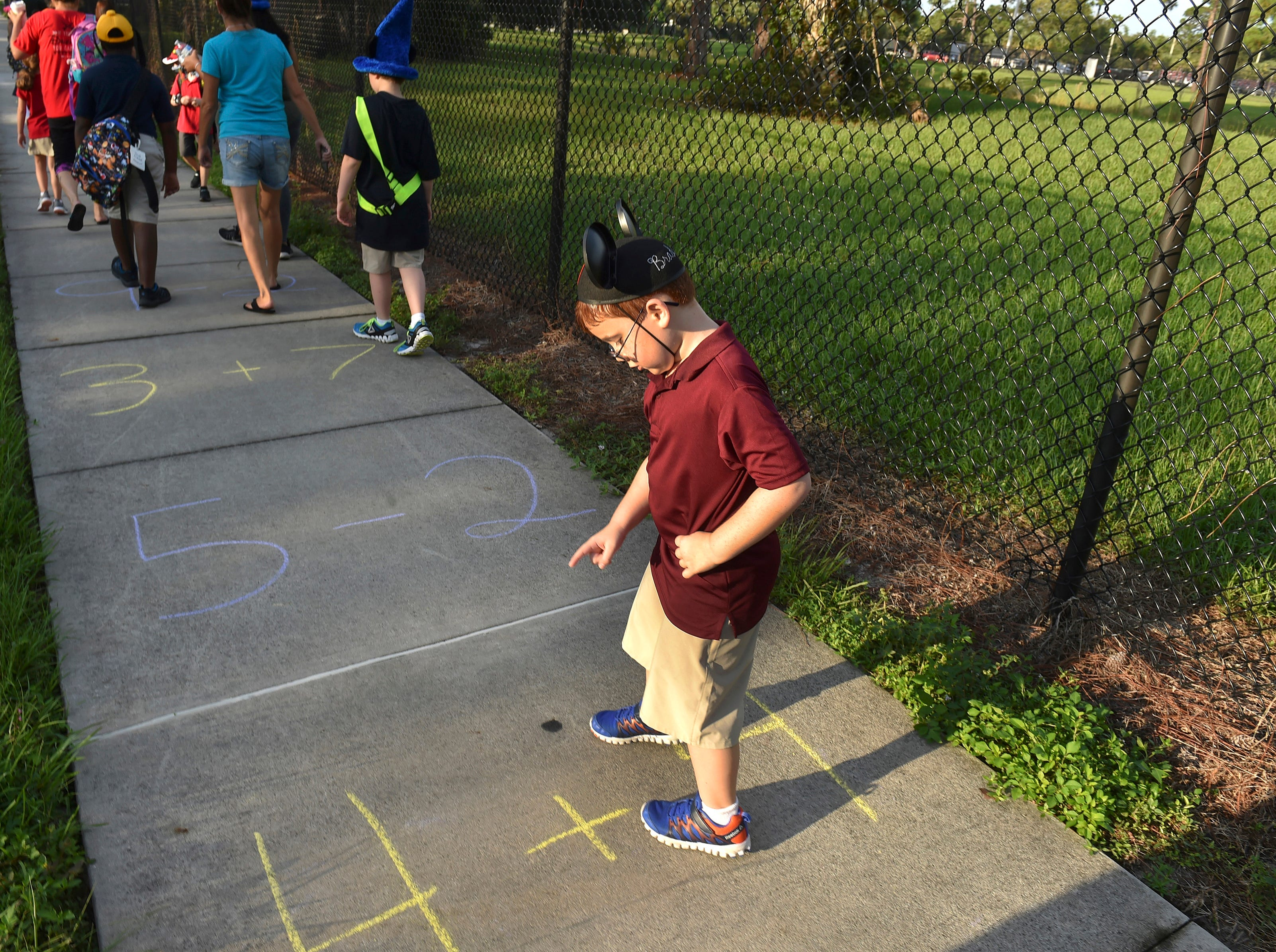 """Brady Trumble, 6, a first grader at Vero Beach Elementary School, stops to solve the math problems along the sidewalk on 16th Avenue during the Walk to School event for students Wednesday morning, Sept. 5, 2018 in Vero Beach. """"This is our walk to school that we do regularly with our PTA (Parent Teacher Association) to promote healthy habits and get kids starting the day with exercise,"""" said Rachel Moree, Assistant Principal at the school. """"We want them to develop healthy habits and spend time with their tribe in the morning, in a way to have healthy hearts."""" . Around 20 students, parents and faculty members walked from the Boys and Girls Club building to the school, with a law enforcement escort, while wearing silly hats and stopping to play the chalk games and answer the challenges inscribed on the sidewalk along the way. """"I love it, I love this school,"""" said Kayla Armand, parent of students Jacob, 4, and Ethan, 8, Armand, (not pictured). """"I love that they are just trying to encourage kids to come to school, encourage parents to be more active in their kid's life and their kid's education, and this is a great way to bring families together."""""""