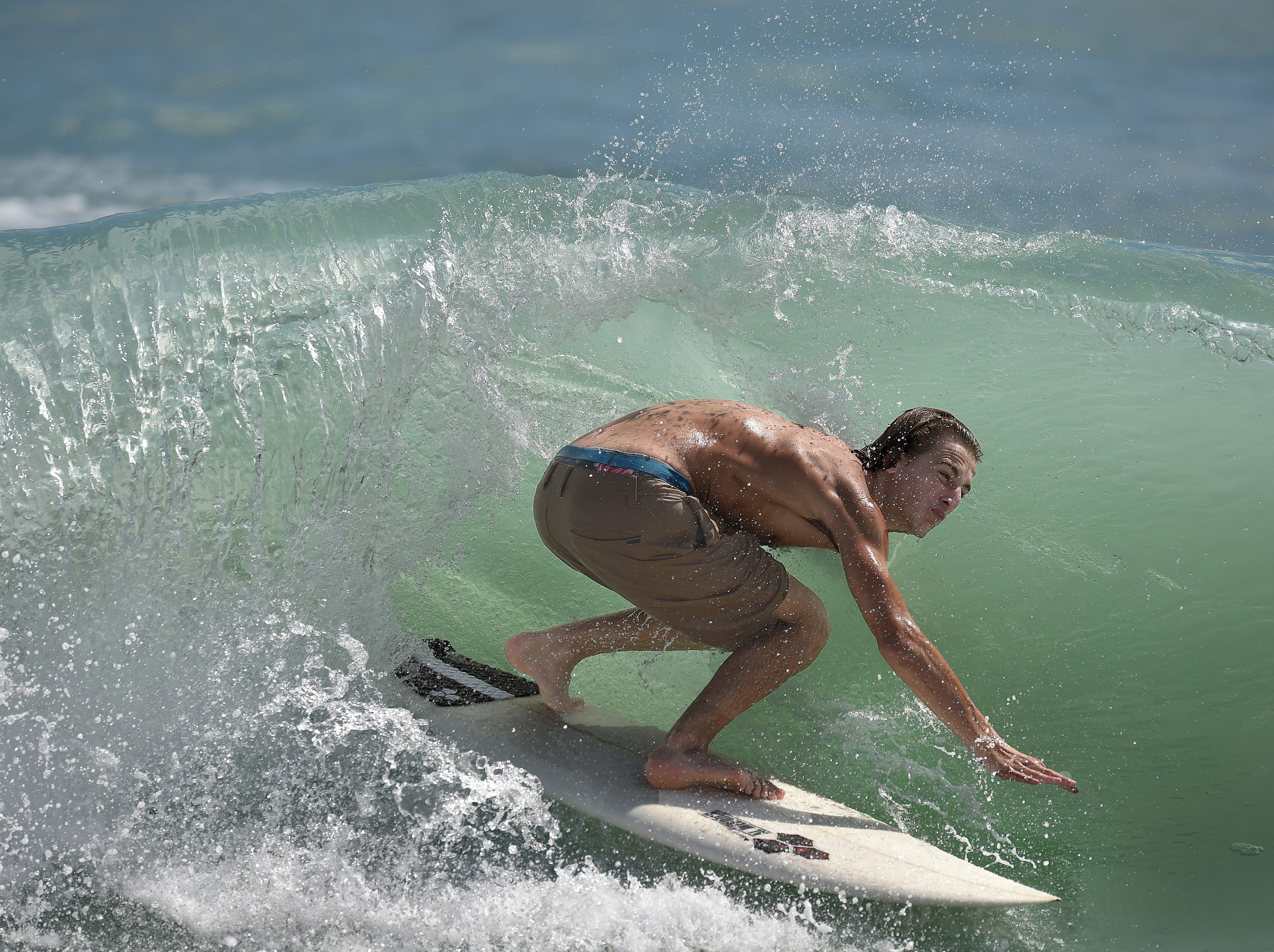 """Noah Aronson, of Miami, catches the inside of a wave surfing on Wednesday, Sept. 12, 2018, at Dollman Park Beachside 9200 South Ocean Drive in Jensen Beach. """"They are fun, they are pretty good,"""" Aronson said about the waves during high tide. Dozens of surfers filled the water including a large group from Miami, riding the  waves from enhanced swells as Hurricane Florence approaches the east coast, aimed at North and South Carolina. Surfers are expecting higher swells creating more powerful waves over the next several days. A high surf advisory has been issued for East Central Florida from 5 p.m. Wednesday until 11 p.m. Thursday, and a high risk for rip currents continues through 8 p.m. Wednesday."""