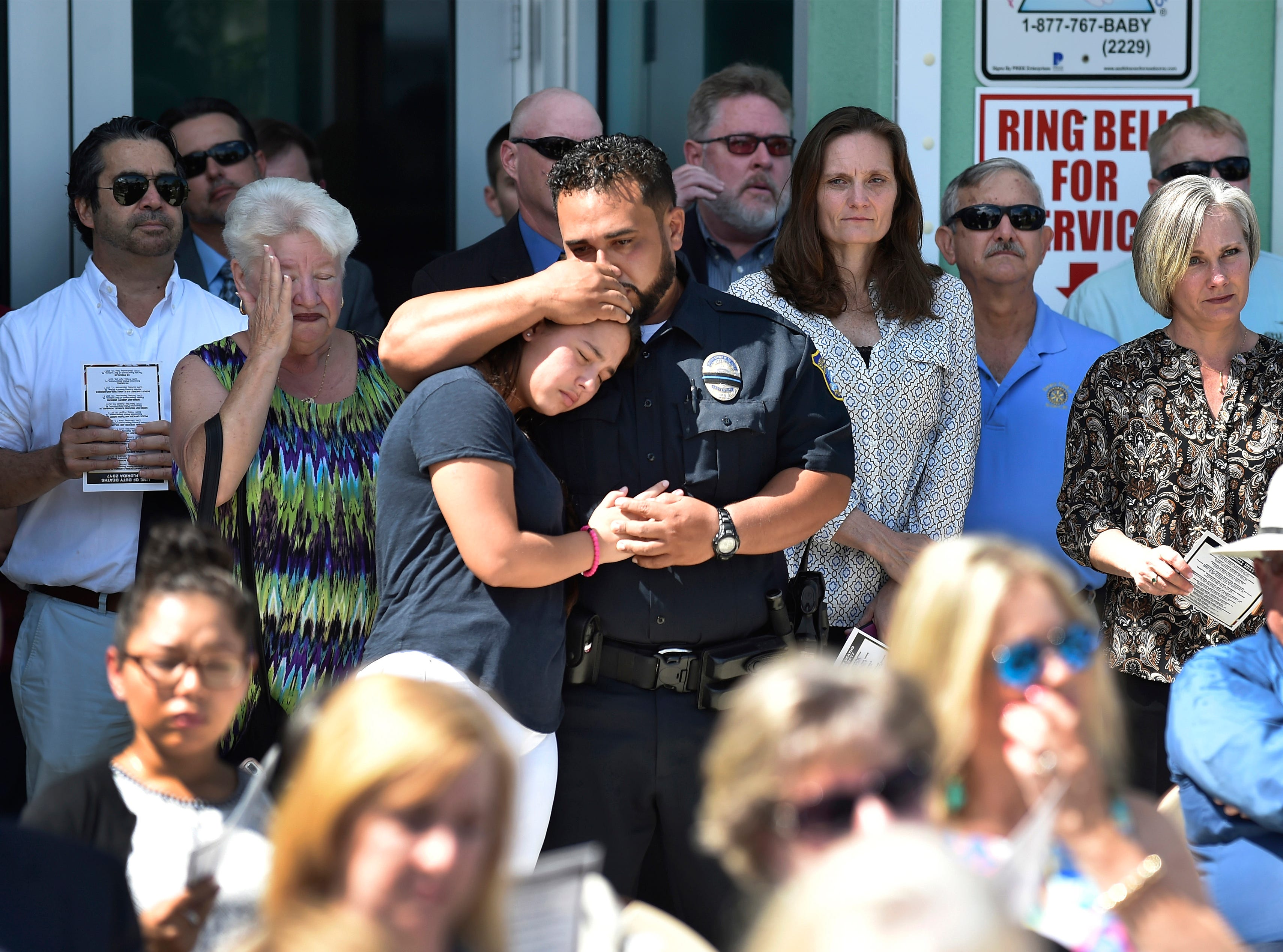 """City of Stuart Police K-9 Officer David Duran (center) and his daughter Naylani, 16, embrace after Officer Duran placed a plaque for his police K-9 Cody on the new K-9 Memorial unveiled during the Martin County Law Enforcement Officer's Memorial Service held Tuesday, May 15, 2018, at the Stuart Police Department. """"I feel pretty honored,"""" said Officer Duran, """"It's really nice to have that to memorialize these guys (K-9) that do a lot of work with us, often forgotten, it's really nice."""" K-9 Cody served eight years with the Stuart Police Department before retiring on June 25, 2015 and passing away December 15, 2017. The memorial service honored all the local law enforcement officers who gave the ultimate sacrifice for the citizens they serve, along with the unveiling of the K-9 memorial statue in front of the entrance of the Stuart Police Department. """"Remembering the law enforcement officers who gave their lives so that their citizens can enjoy the freedom and safety is very important,"""" said Stuart Police Chief David Dyess. """"We're also doing a K-9 memorial dedication here today where we honor our K-9 partners in our career, and I think it's also evident that we need to remember them as we do our law enforcement officers who have given the ultimate sacrifice."""""""