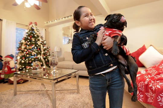 Jacqueline Rosales, 11 holds her pug in her Horizon City home. She has been battling leukemia since 2016.