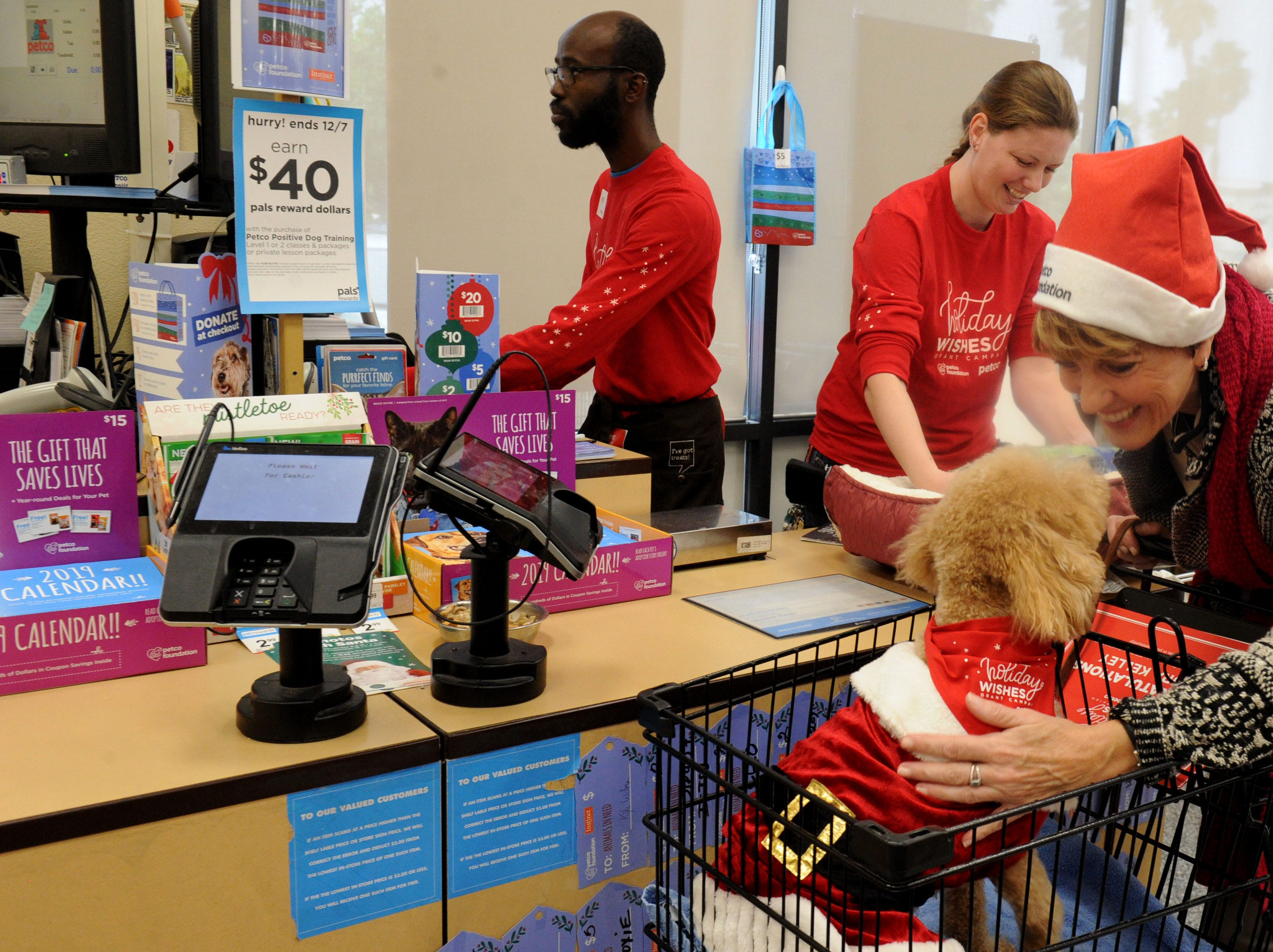 "Maura Kelley and her dog Chenko spend $50 Wednesday in a shopping spree at Petco in Camarillo. Will Hill, left, and Cadie Bandy, Petco store leader, help check out Kelley. Chenko was named after Kelley's husband, Ventura County sheriff's Deputy Yevhen ""Eugene"" Kostiuchenko, who died in the line of duty."