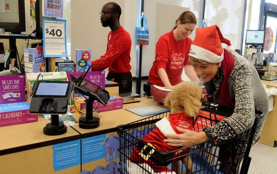 """Maura Kelley and her dog Chenko spend $50 Wednesday in a shopping spree at Petco in Camarillo. Will Hill, left, and Cadie Bandy, Petco store leader, help check out Kelley. Chenko was named after Kelley's husband, Ventura County sheriff's DeputyYevhen """"Eugene"""" Kostiuchenko, who died in the line of duty."""