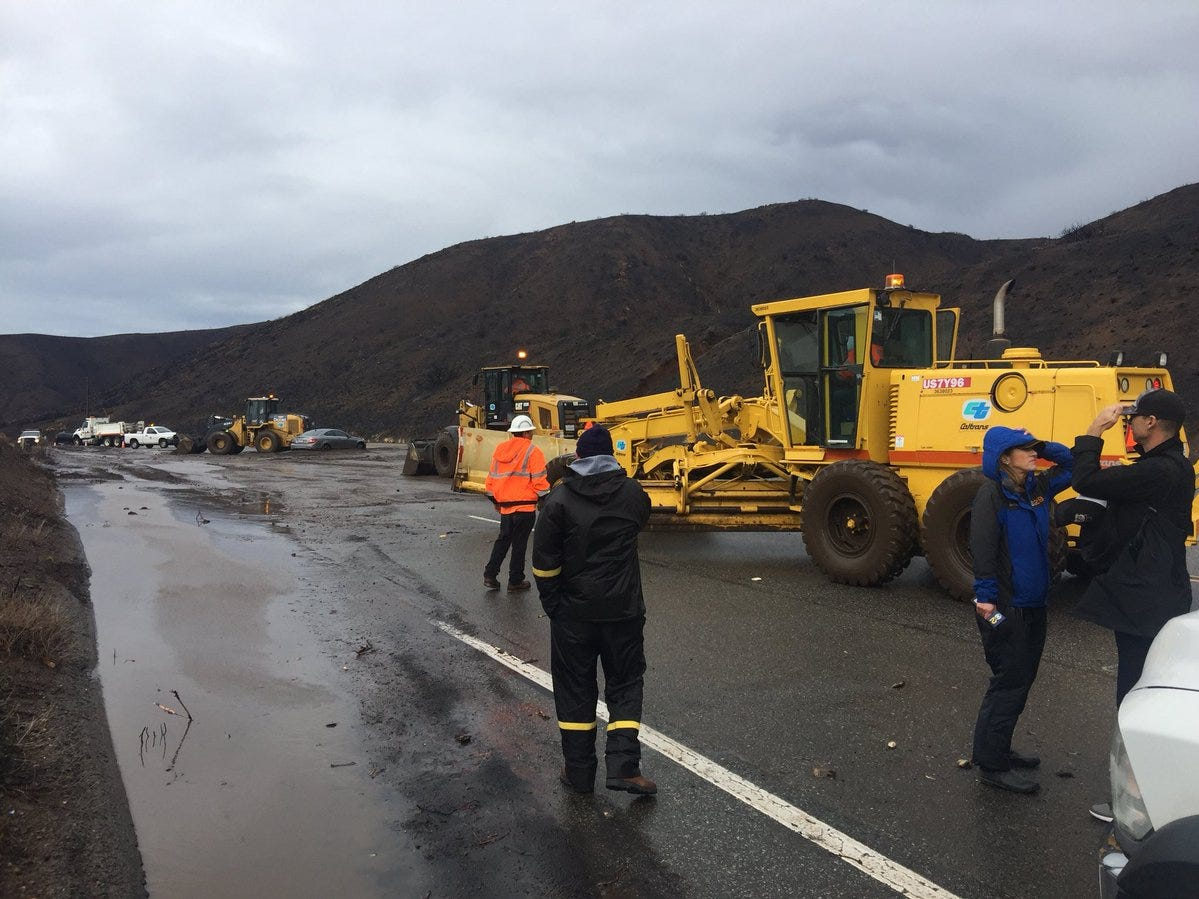 Heavy equipment is used on Pacific Coast Highway Thursday morning after a small mudslide was caused by rain.