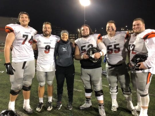 Mikala Cvijanovich, 21, the strength and mobility coach for the Ventura College football team poses with players Blake Walker, Bradley Taylor, Dane Nelson, Tyler Orsini and Kyle Howard (left to right) after the Pirates won the Southern California championship at Riverside on Dec. 1.
