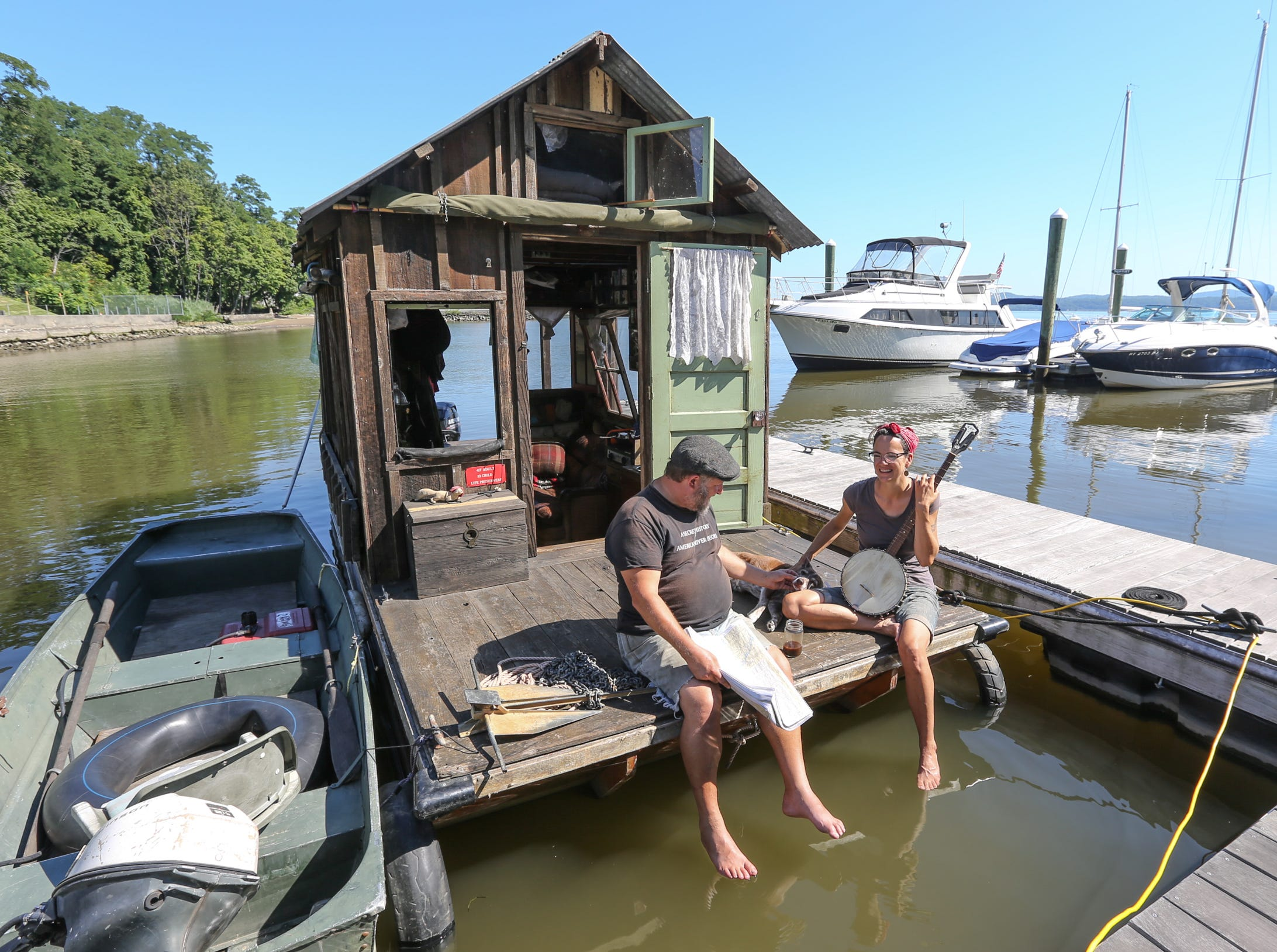 """Wes Modes, of Santa Cruz, Calif., center, and ship mate Lauren Benz, with their dog  Hazel sit on the bow the Shantyboat """"Dotty"""" at the Admiral's Cove Marina in Haverstraw on Friday, July 20, 2018.  Modes and Landis stopped in Haverstraw on their way from Albany to Brooklyn."""