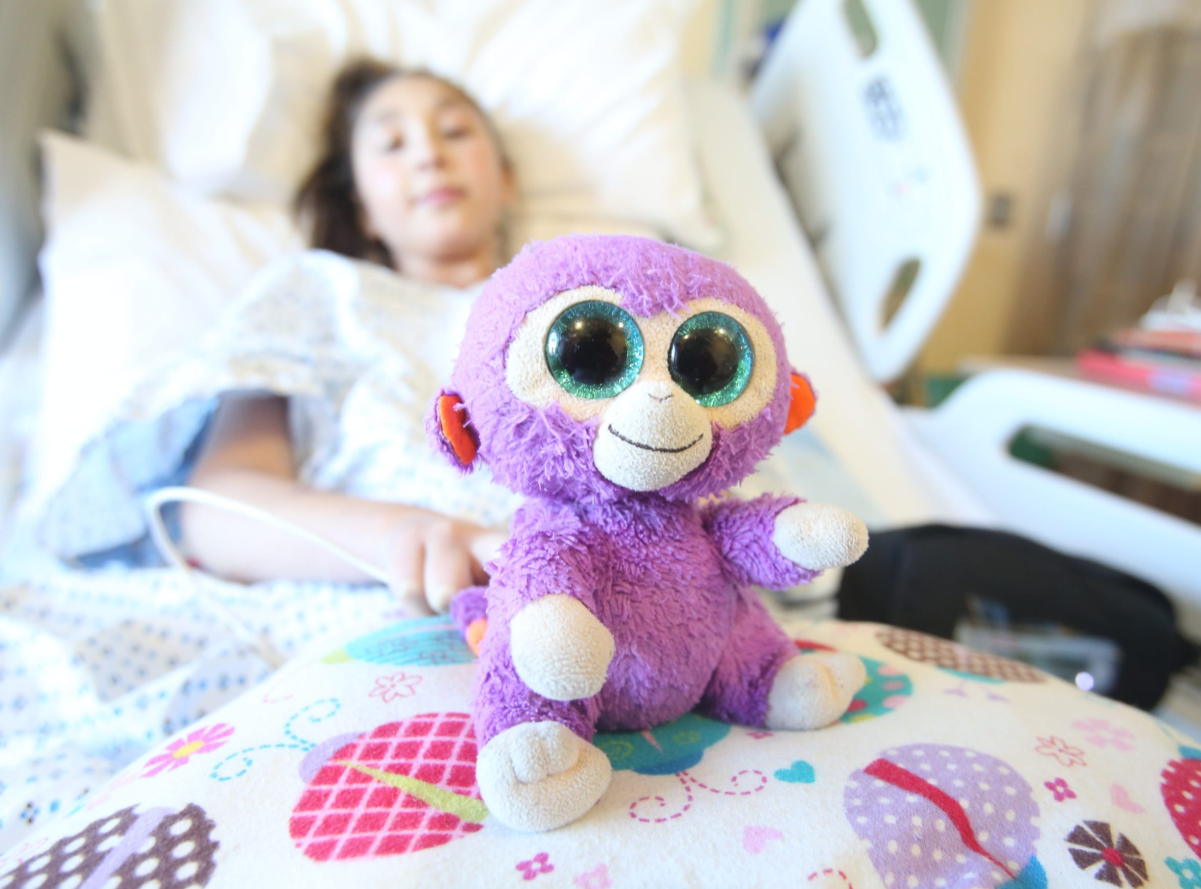 Grape, the stuffed monkey sits in the bed with Isabella Munoz, 12, at Morgan Stanley Children's Hospital in Manhattan Jan. 25, 2018. Bella has been in the hospital since Jan. 6, awaiting open-heart surgery, and the stuffed monkey has never left her bedside since being diagnosed with a heart condition two years ago.