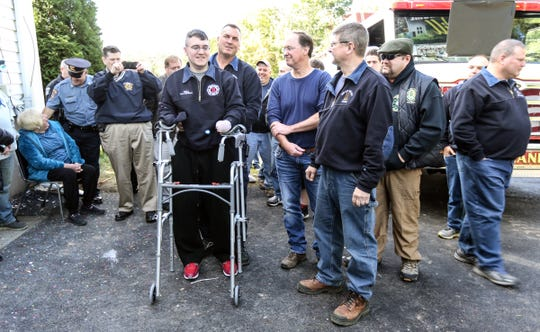Willy McCue, 20, uses a customized walker with assistance from New City Fire Department Asst. Chief Rich Willows, on the driveway of his his New City home on Friday, October 19, 2018.