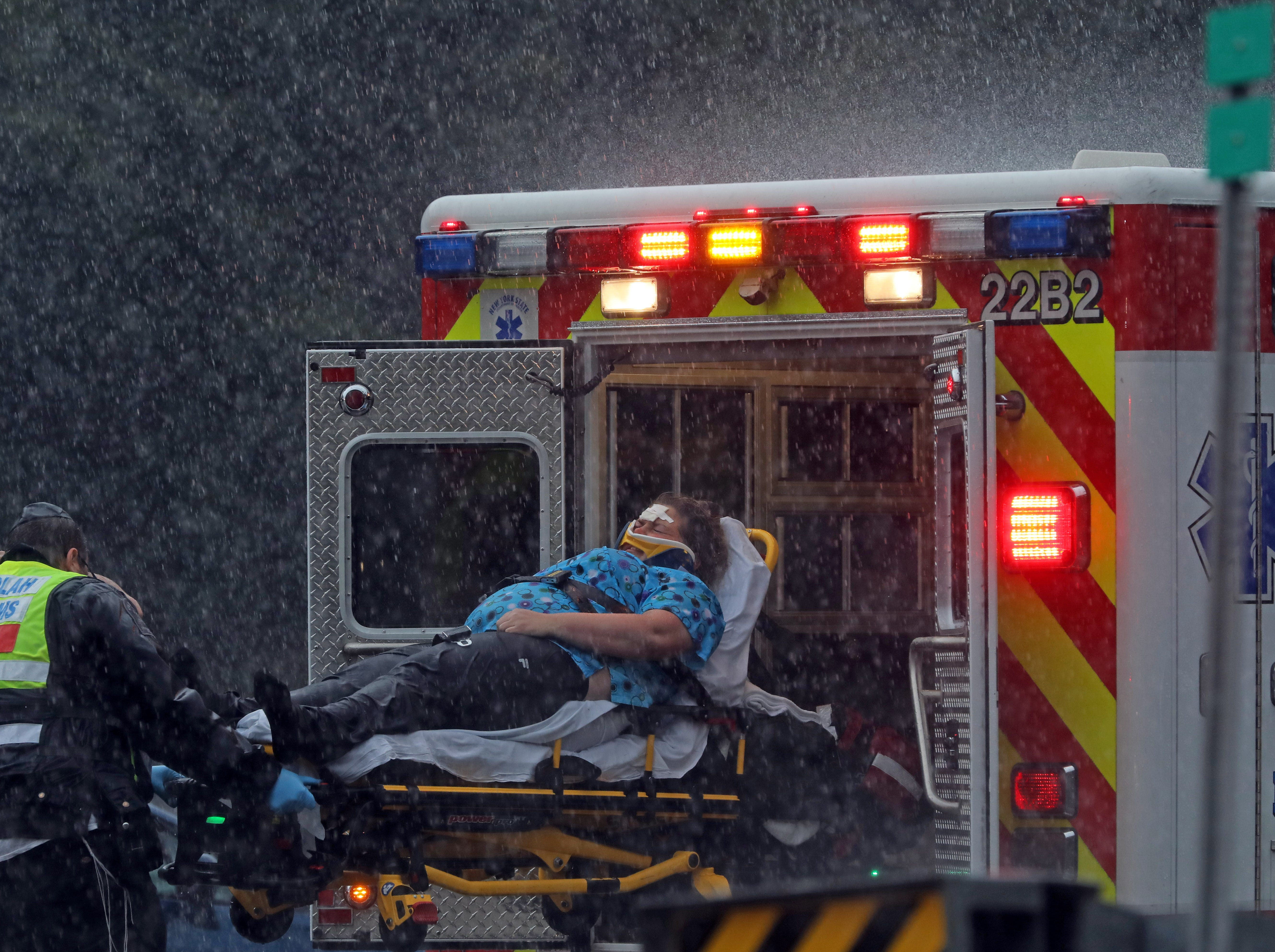 A woman in a red car is help by the paramedic after being in a two car accident on I-87 Southbound in Spring Valley on Thursday Oct. 11, 2018. Two people were taken by ambulance to the hospital.