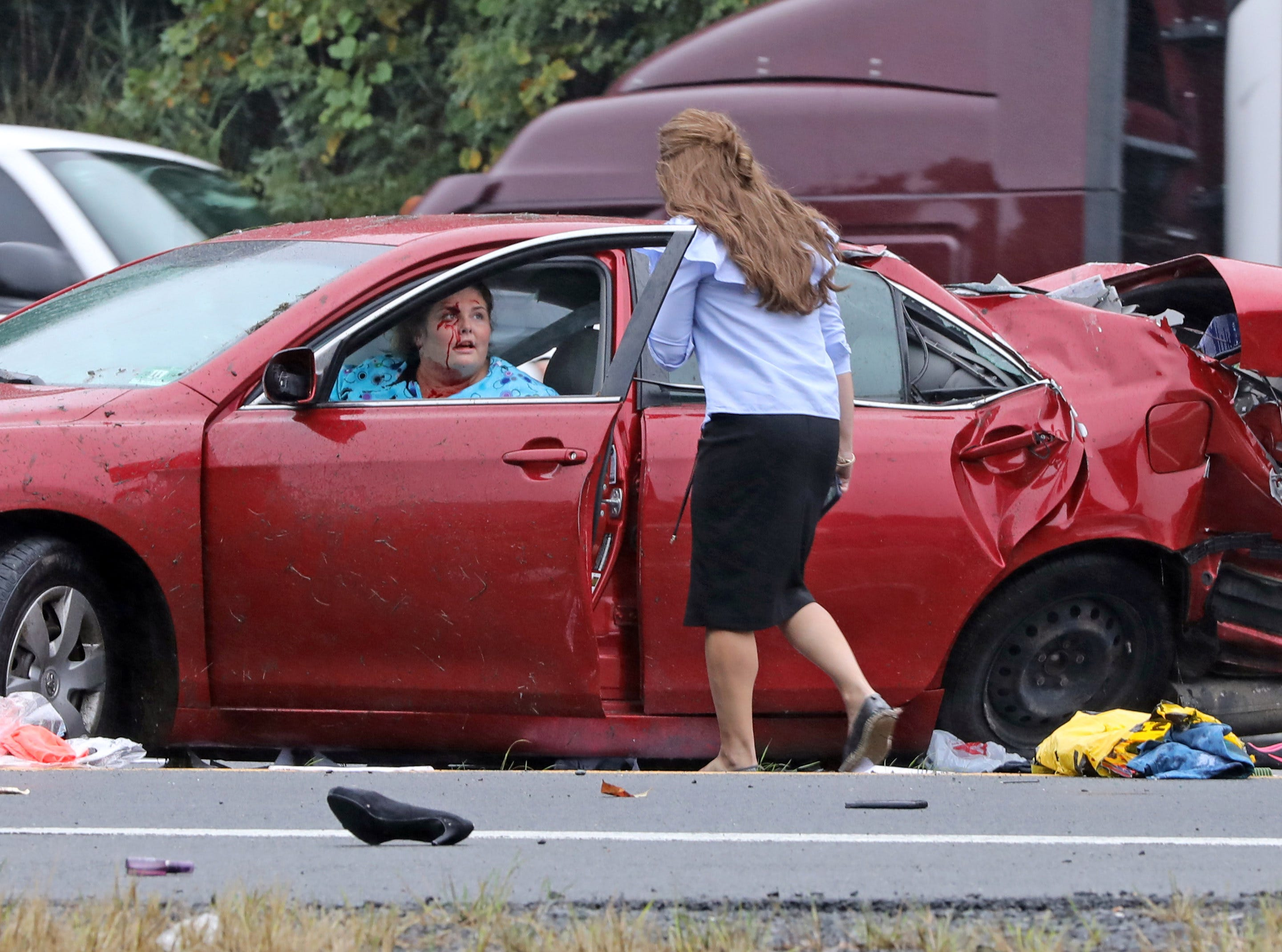 A woman in a red car is talks to passerby who helps her  after being in a two car accident on I-87 Southbound in Spring Valley on Thursday Oct. 11, 2018. Two people were taken by ambulance to the hospital.