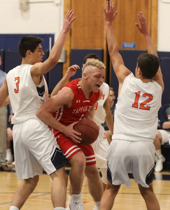 Tappan Zee's Oziah DeLoatch (1) goes up for two with Horace Greeley's Chris Melis (3) and Chris Saverborn (12) guarding him during boys basketball game at the high school in Chappaqua Dec. 5, 2018. Tappan Zee beats Horace Greeley 49-46.
