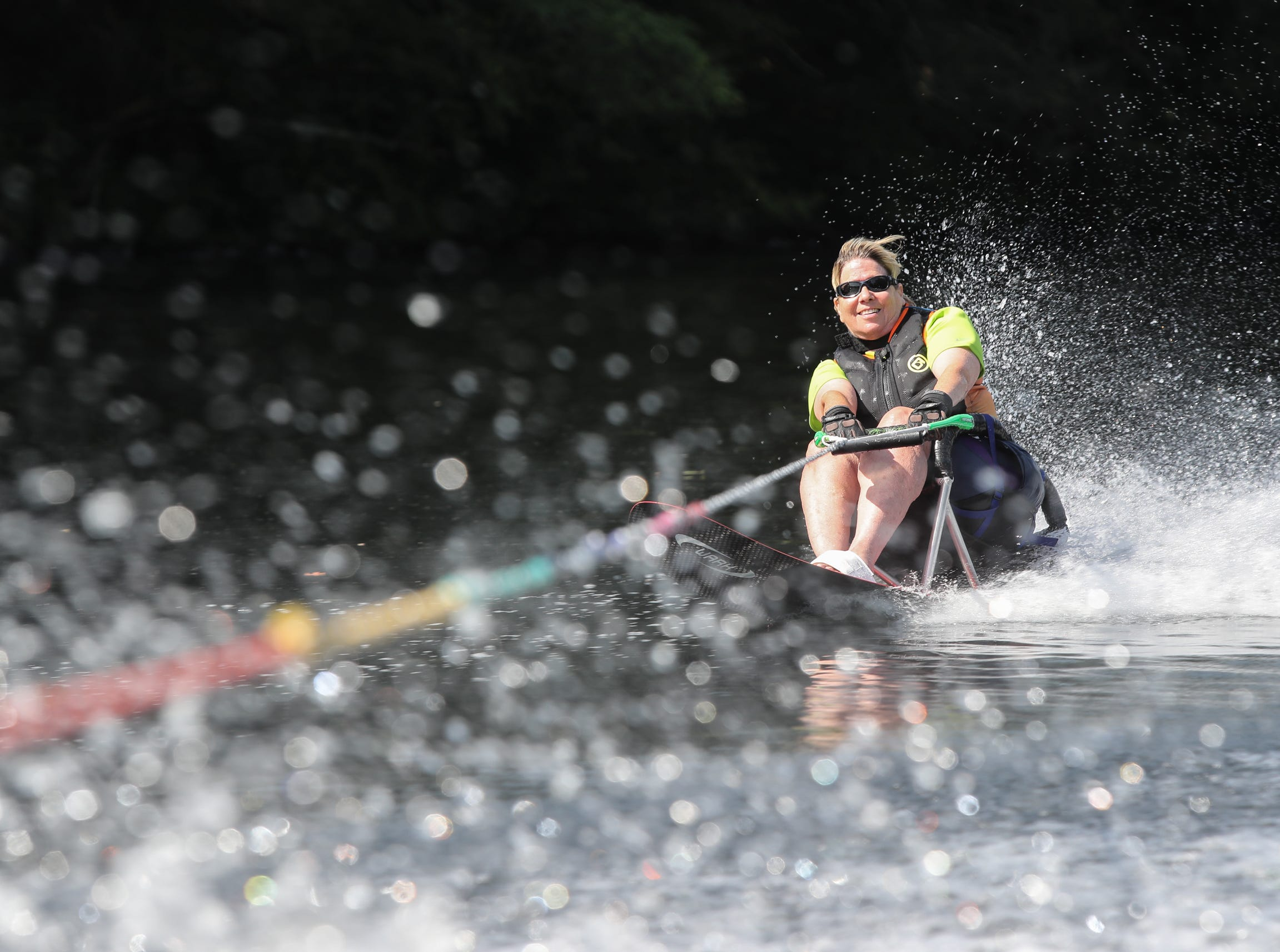 Caren Landis, 63, from Valley Cottage uses a specialized ski with a seat to water skis on a section of the Pootatuck River in Sandy Hook, Conn. on Friday, July 13, 2018.  Landis suffered a spinal cord injury, is paralyzed from her mid-torso and relys on a wheelchair.