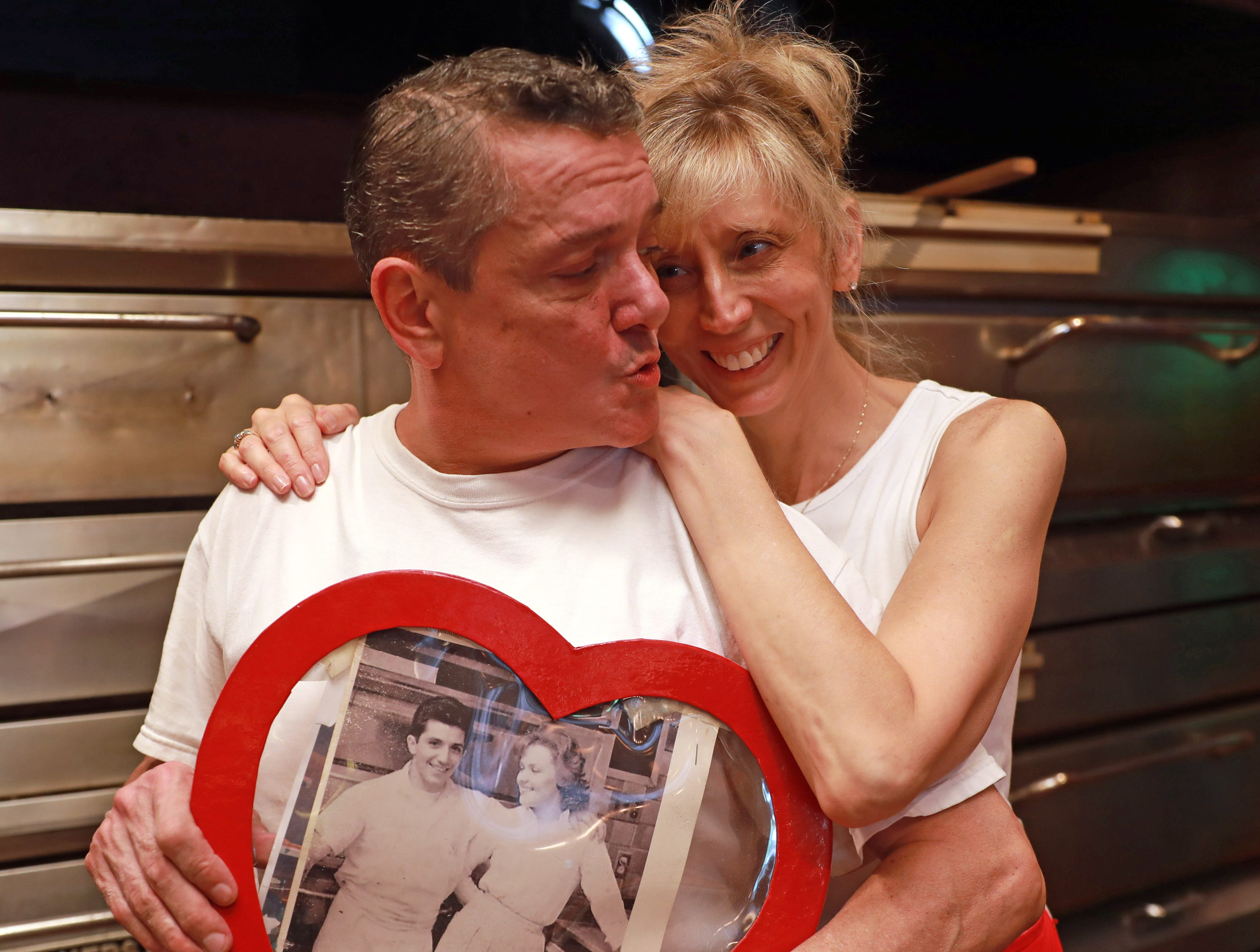 """Frankie Colandrea, the owner of Martio's Pizza in Nanuet on Aug. 21, 2018, kisses his wife, Cindy while holding a photo of his parents, Frank """"Martio"""" and Lois Colandrea, who founded the place in 1958 in Spring Valley before moving it to Nanuet in 1975."""
