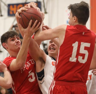 Tappan Zee's Aidan Cunney (5) and Charlie Garrison (15) battle with Horace Greeley's Nicholas Townsend (42) for a rebound during boys basketball game at the high school in Chappaqua Dec. 5, 2018. Tappan Zee beats Horace Greeley 49-46.