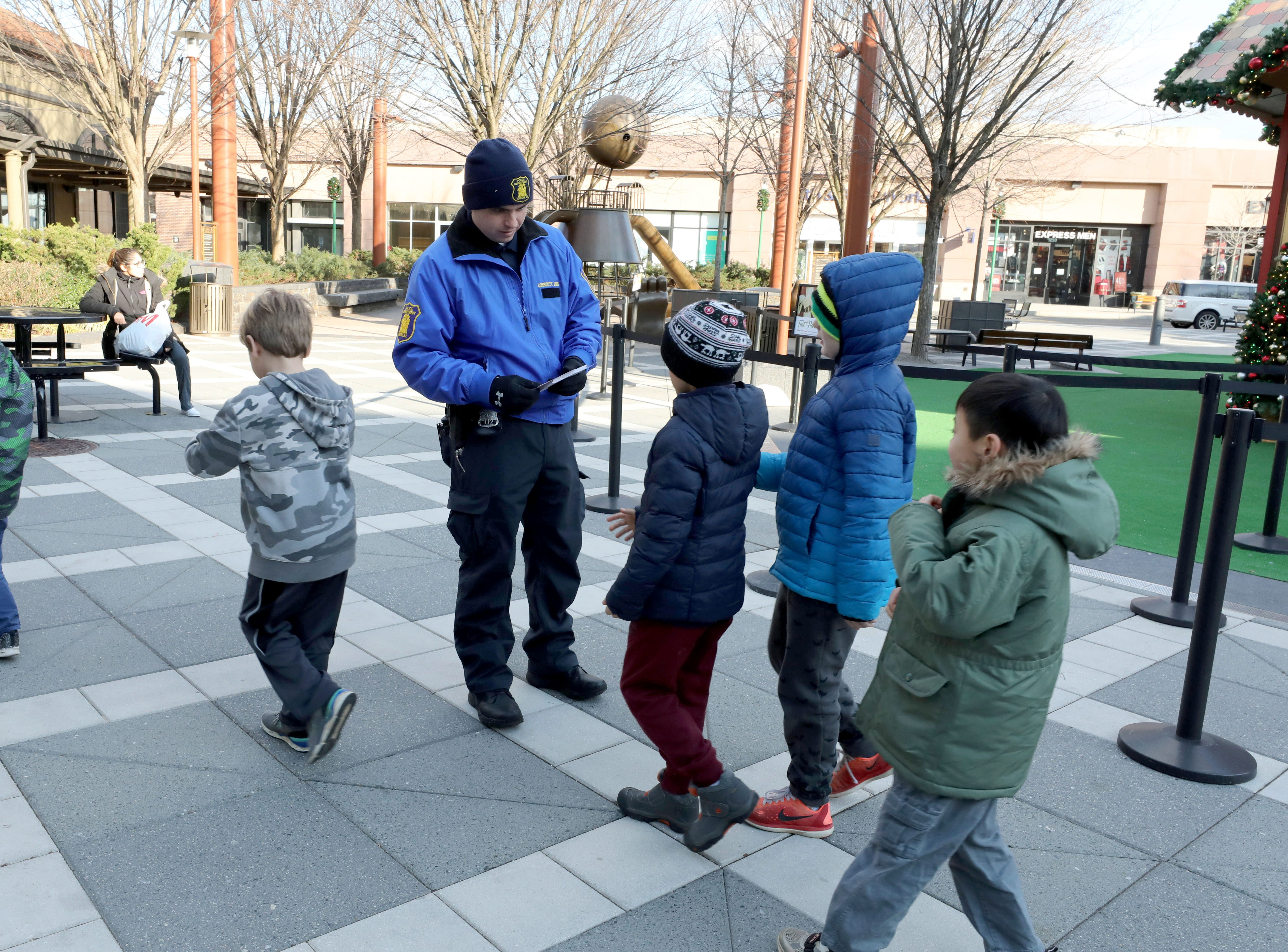 "Yonkers Police Officer Charles ""CJ"" Bowen with the community affairs division, hands out information cards to children, during a ""Stop & Shake"" program at Ridge Hill in Yonkers, Dec. 6, 2018. The Stop & Shake is a city initiative created by resident Hector Santiago in partnership with the YPD, to build strong personal relationships between law enforcement and the community they serve."