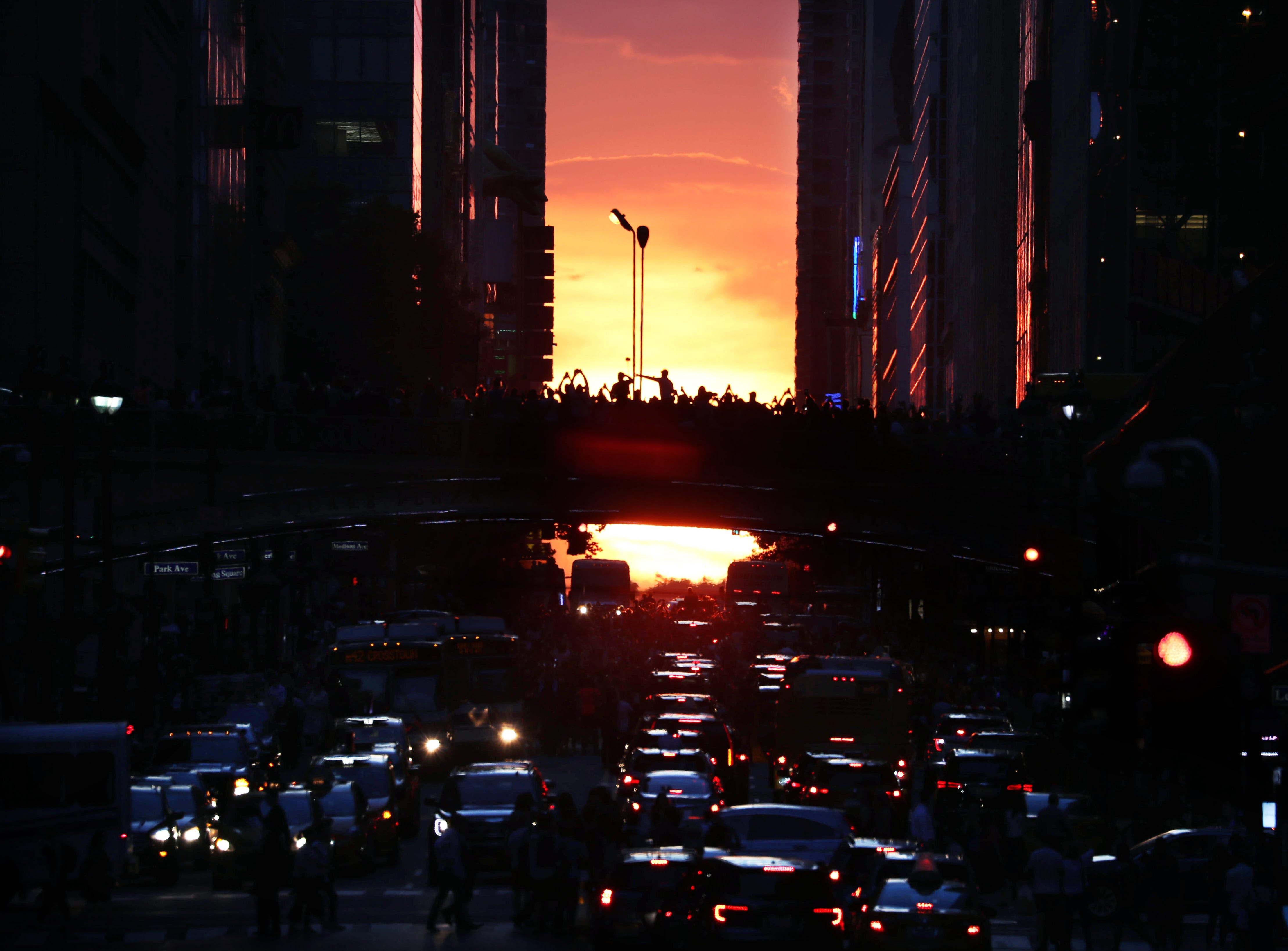 Thousands stand on and above 42nd Street and on many cross streets in Manhattan July 12, 2018 to glimpse Manhattanhenge, the occurrence when the sun sets in alignment with the streets that run east to west on Manhattan's street grid.