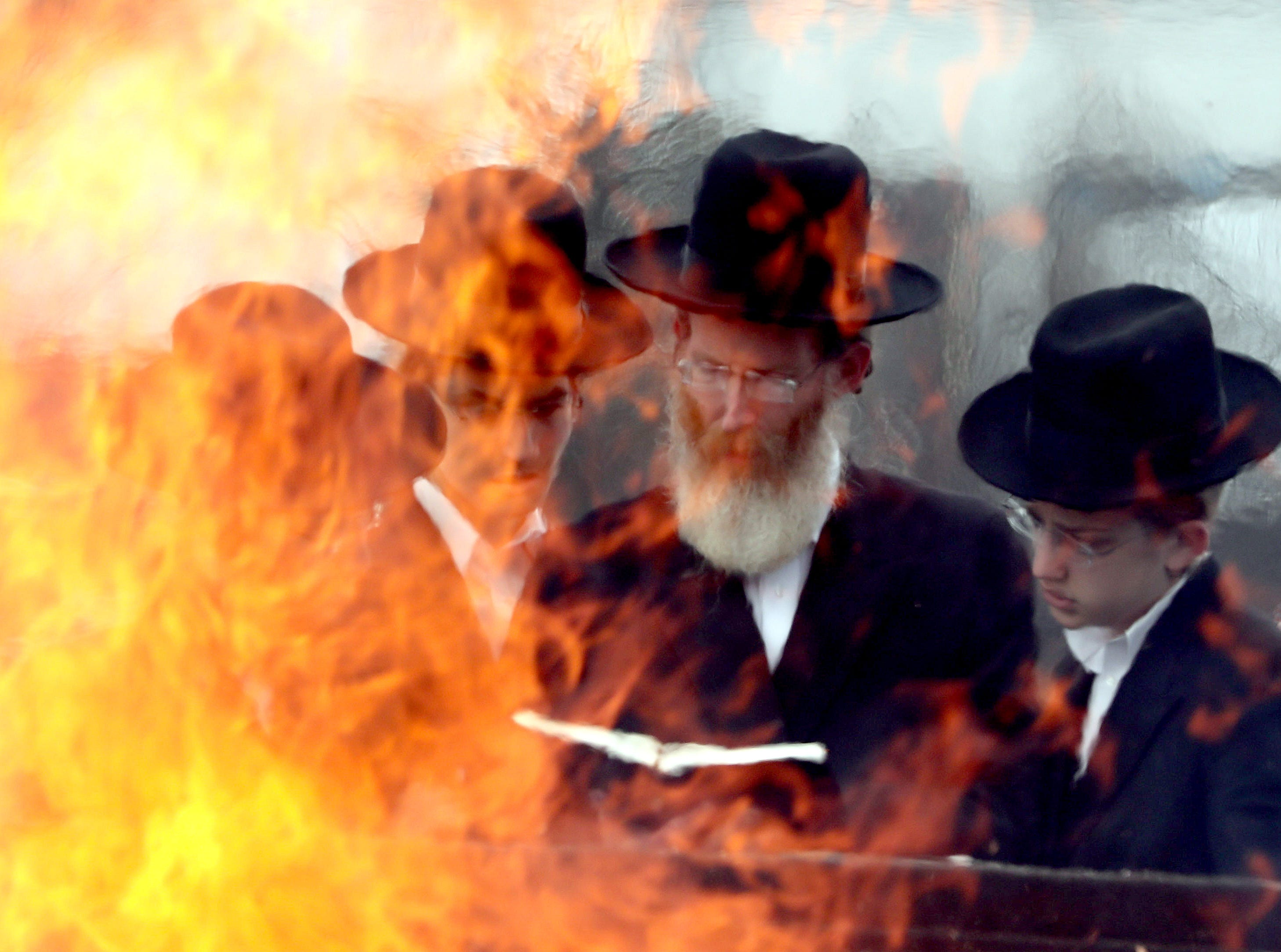 Orthodox Jewish man and young boys read from scriptures as members of the community throw bread products into a fire at the old drive-in theater on route 59 in Spring Valley March 30, 2018 before the start of Passover, which begins at sundown. During the eight days of Passover, Jews abstain from eating bread and other leavened foods in commemoration of the Israelites who, when fleeing slavery in ancient Egypt, didn't have time to bake bread, and only had unleavened bread to take with them as they fled slavery. Thousands of Orthodox Jews threw their bread products into fires in several locations in Monsey and Spring Valley.