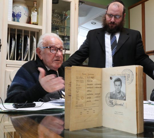 Michael Marder, 93, a Holocaust survivor of nine concentration camps, with Rabbi Shmuel Gancz, looks over old photographs  in his Airmont home on Thursday.