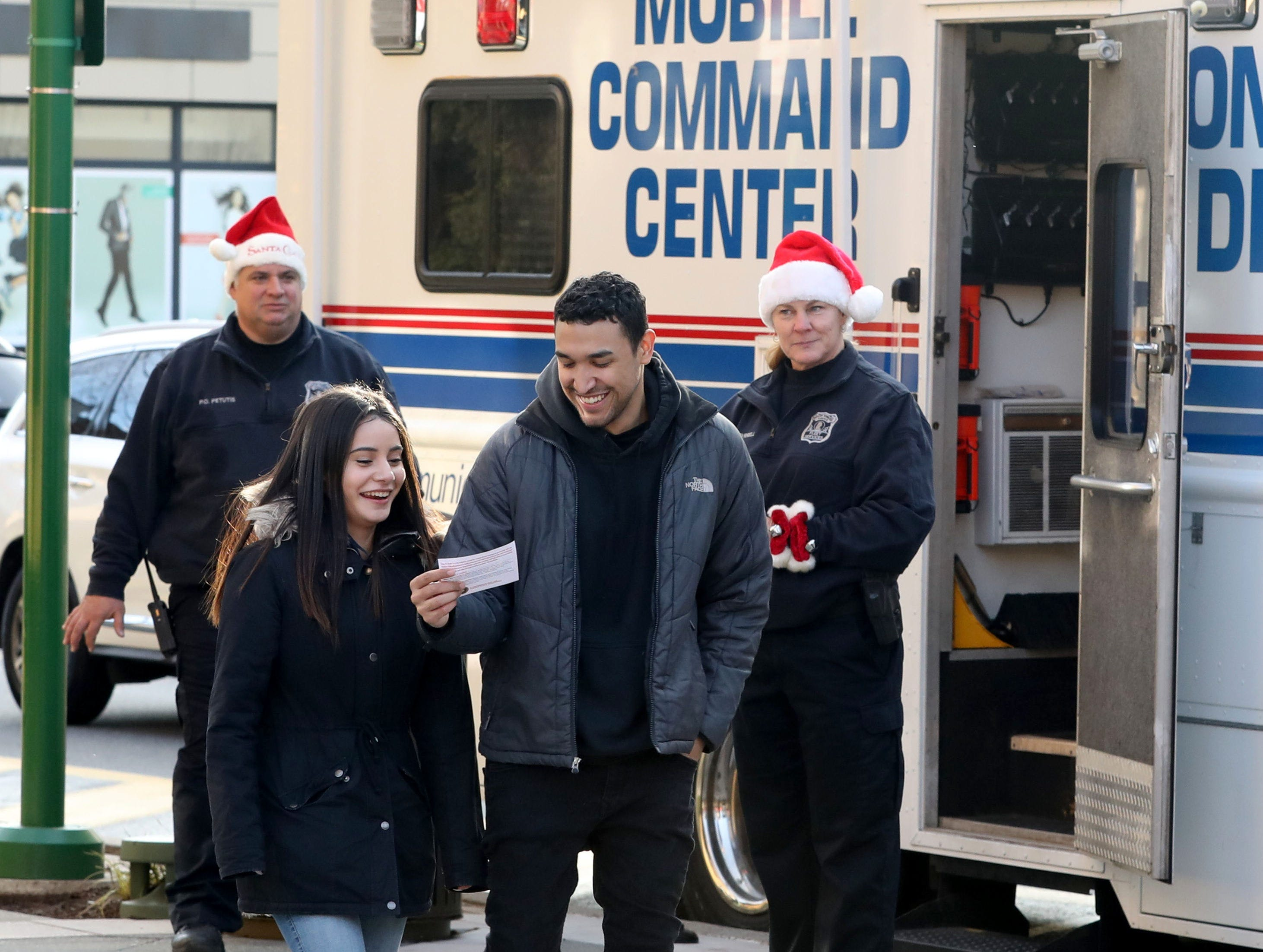 "Tatyana Rivera and Justin Hidalgo look over an information card they received from Yonkers Police Officers Linda Tyrell and John Petutis, during a ""Stop & Shake"" program at Ridge Hill in Yonkers, Dec. 6, 2018. The Stop & Shake is a city initiative created by resident Hector Santiago in partnership with the YPD, to build strong personal relationships between law enforcement and the community they serve."