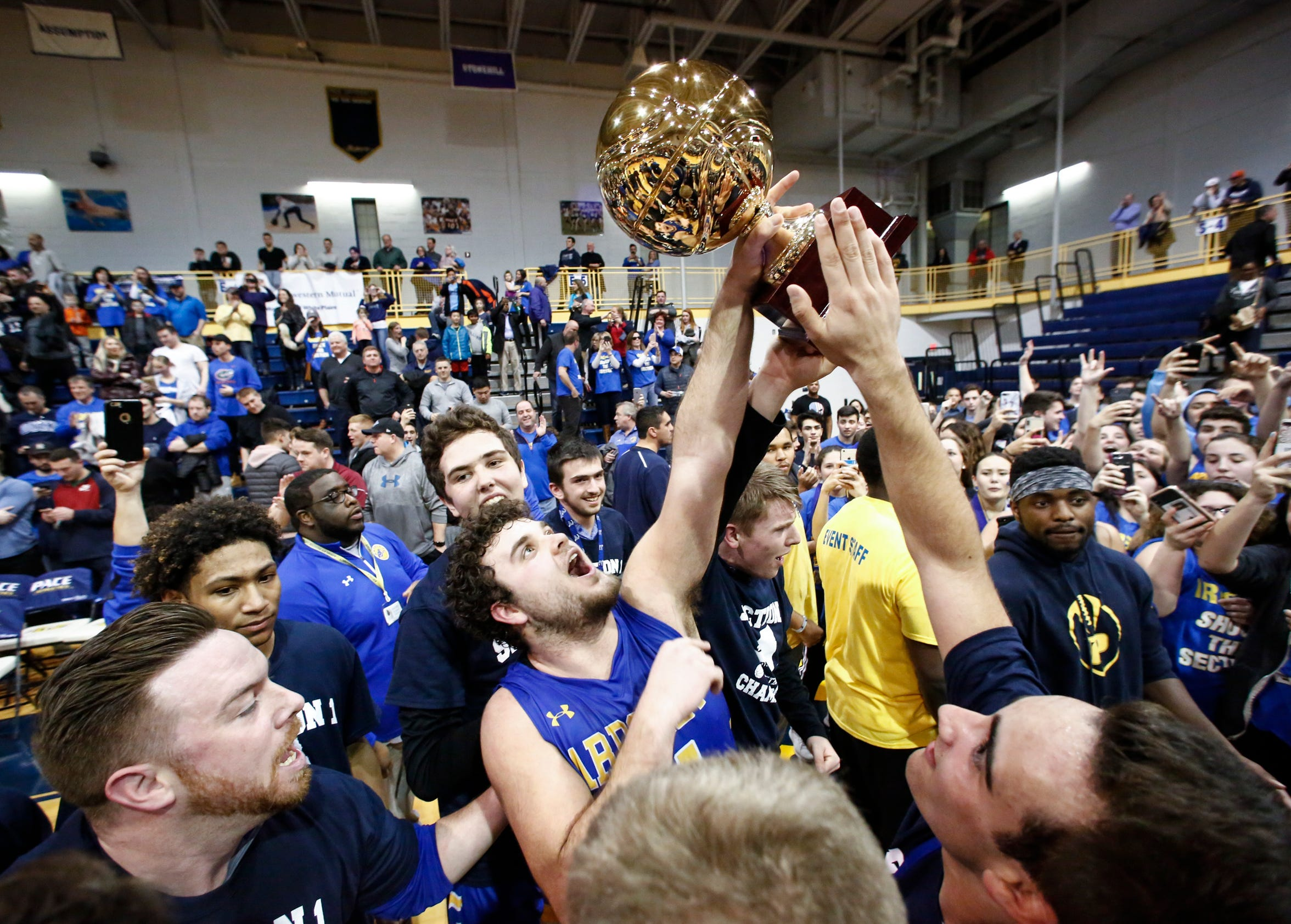 Ardsley's Julian McGarvey (21) center hoists the gold ball after sinking a more than 70-foot shot to defeat Tappan Zee 52-51 in the final seconds of the the boys Class A championship basketball game at Pace University in Pleasantville on Saturday, March 3, 2018.