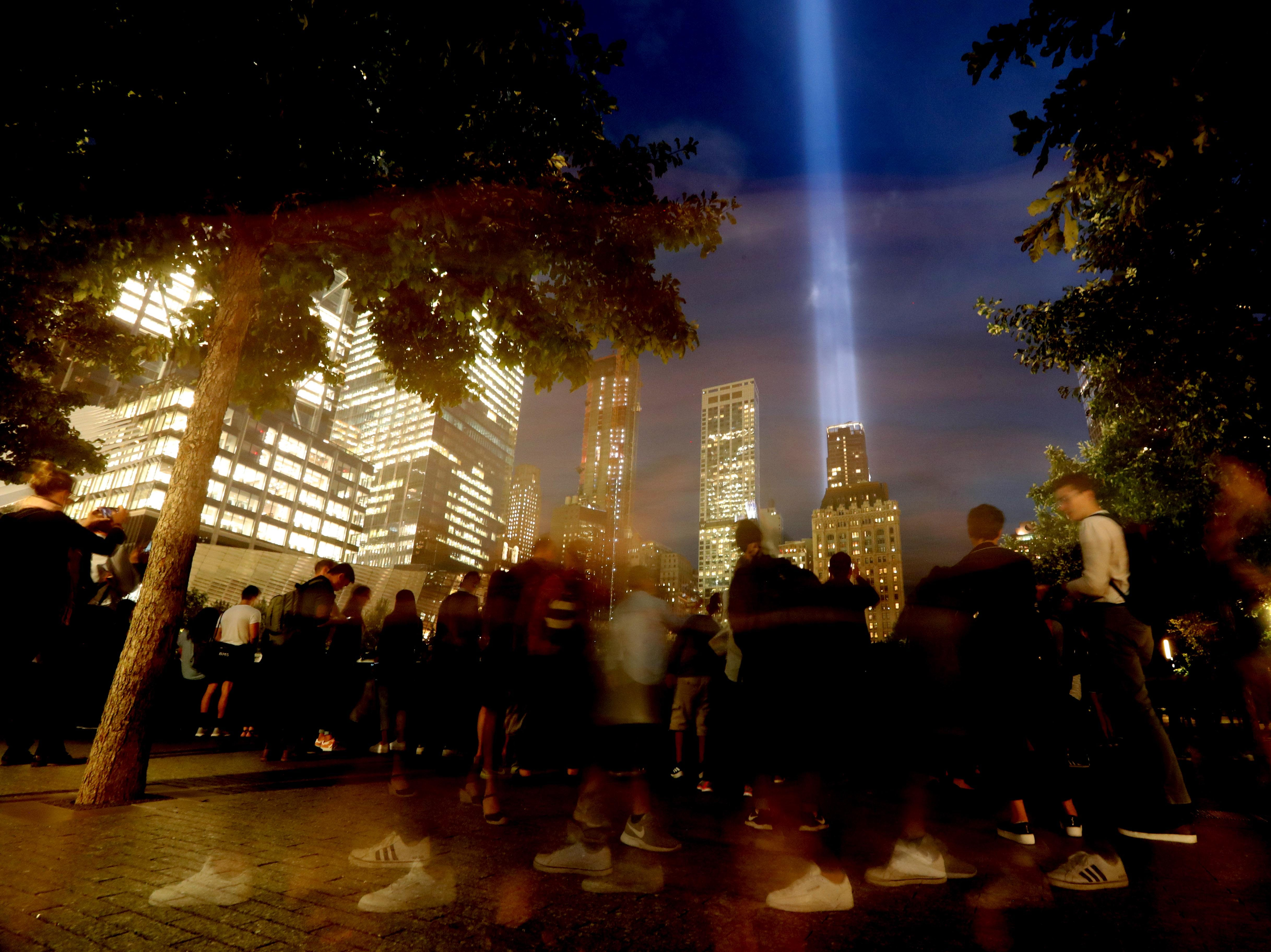 Visitors to the The National September 11 Memorial in New York City take in the Tribute in Light Tuesday, Sept. 11, 2018.  Thousands visited the memorial on the 17th anniversary of the attacks of Sept. 11, 2001.