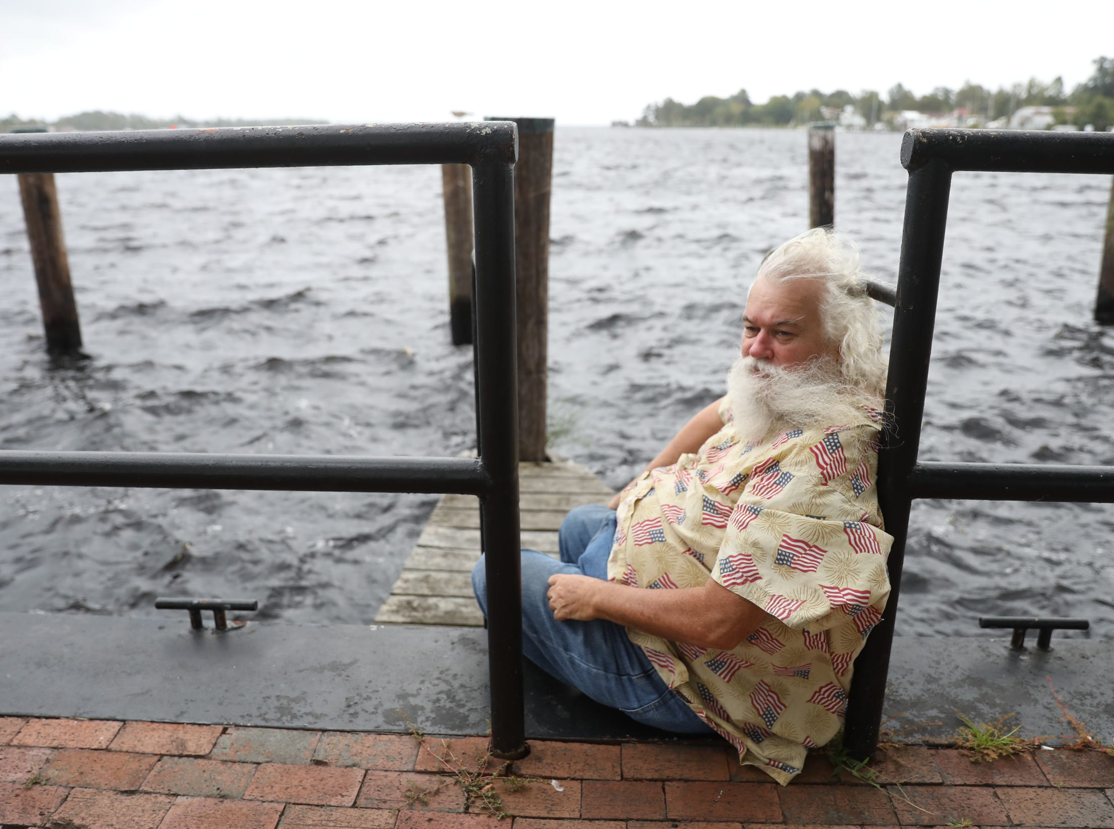 Daniel Harris sits on the bulkheasd of  Mariners' Wharf Park in downtown Elizabeth City, North Carolina on Thursday, September 13, 2018.  Harris plans to ride out the storm, like he has for all other storms, in his near-by home.