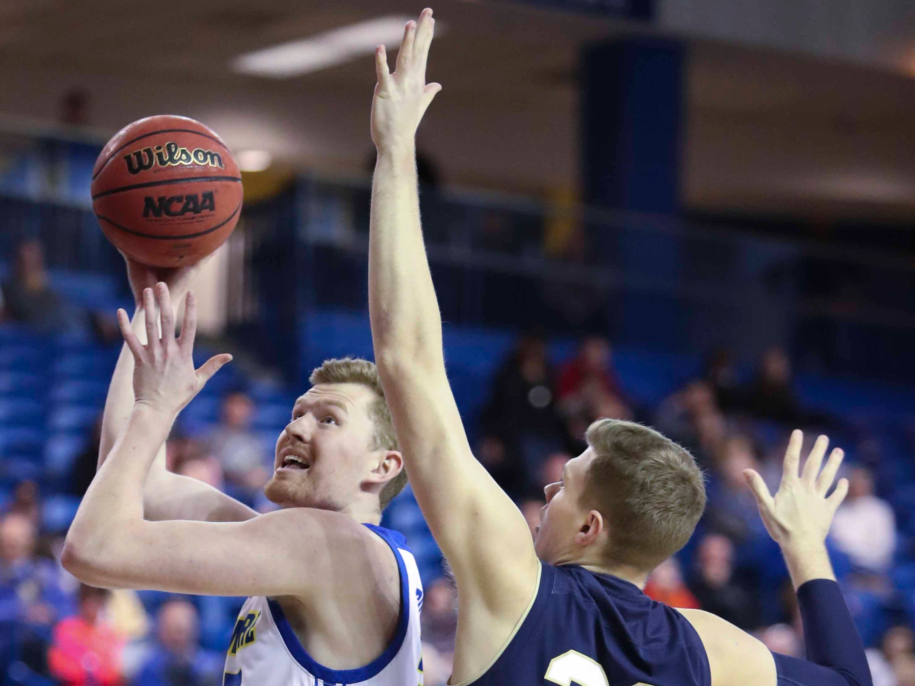 Delaware's Collin Goss looks to the basket past Navy's Luke Loehr in the first half at the Bob Carpenter Center Wednesday.