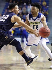 Navy's Cam Davis (left) defends against Delaware's Ithiel Horton in the first half at the Bob Carpenter Center Wednesday.
