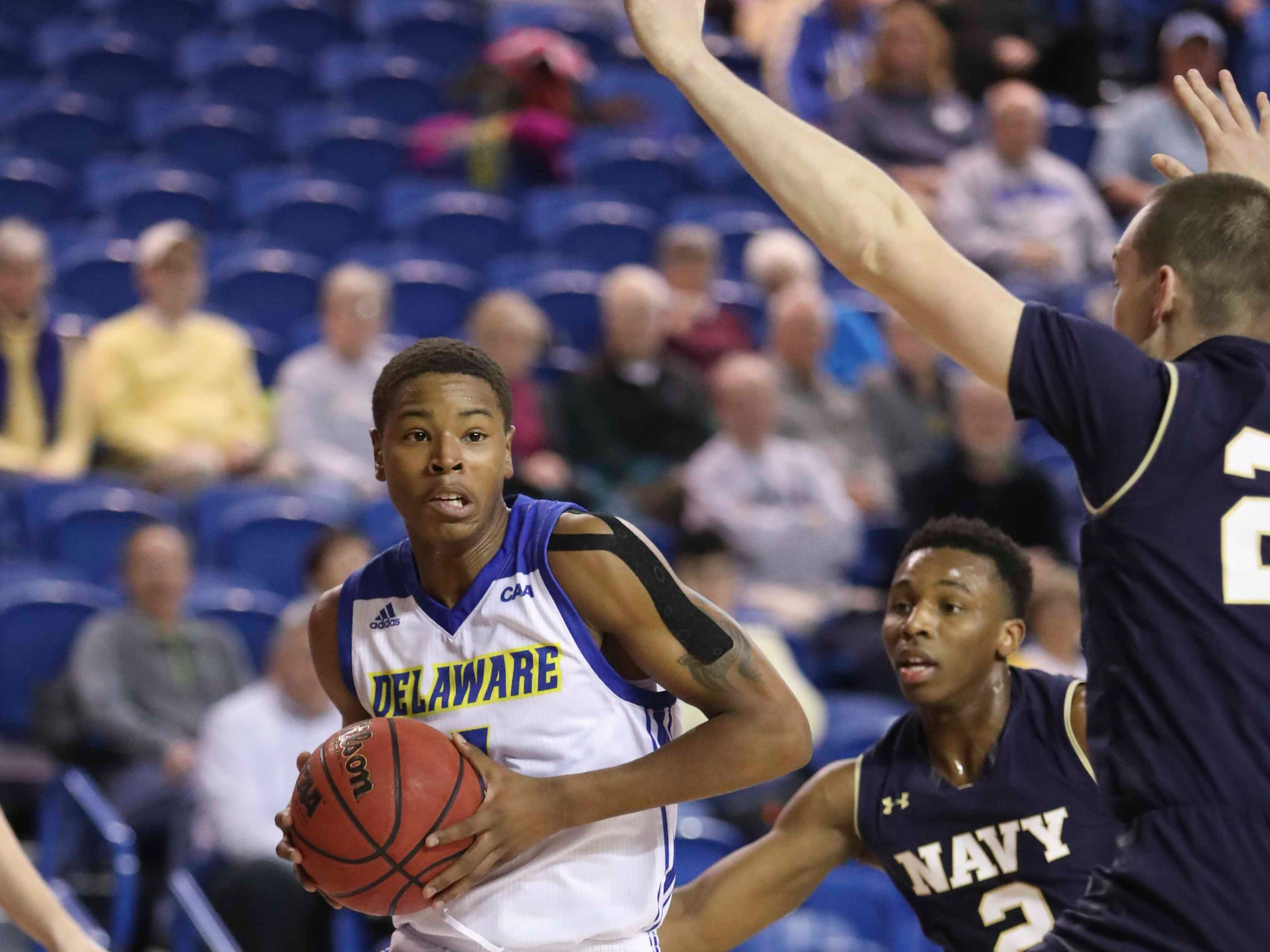 Delaware's Kevin Anderson (left) drives against Navy's Hasan Abdullah (2) and Greg Summers in the first half at the Bob Carpenter Center Wednesday.