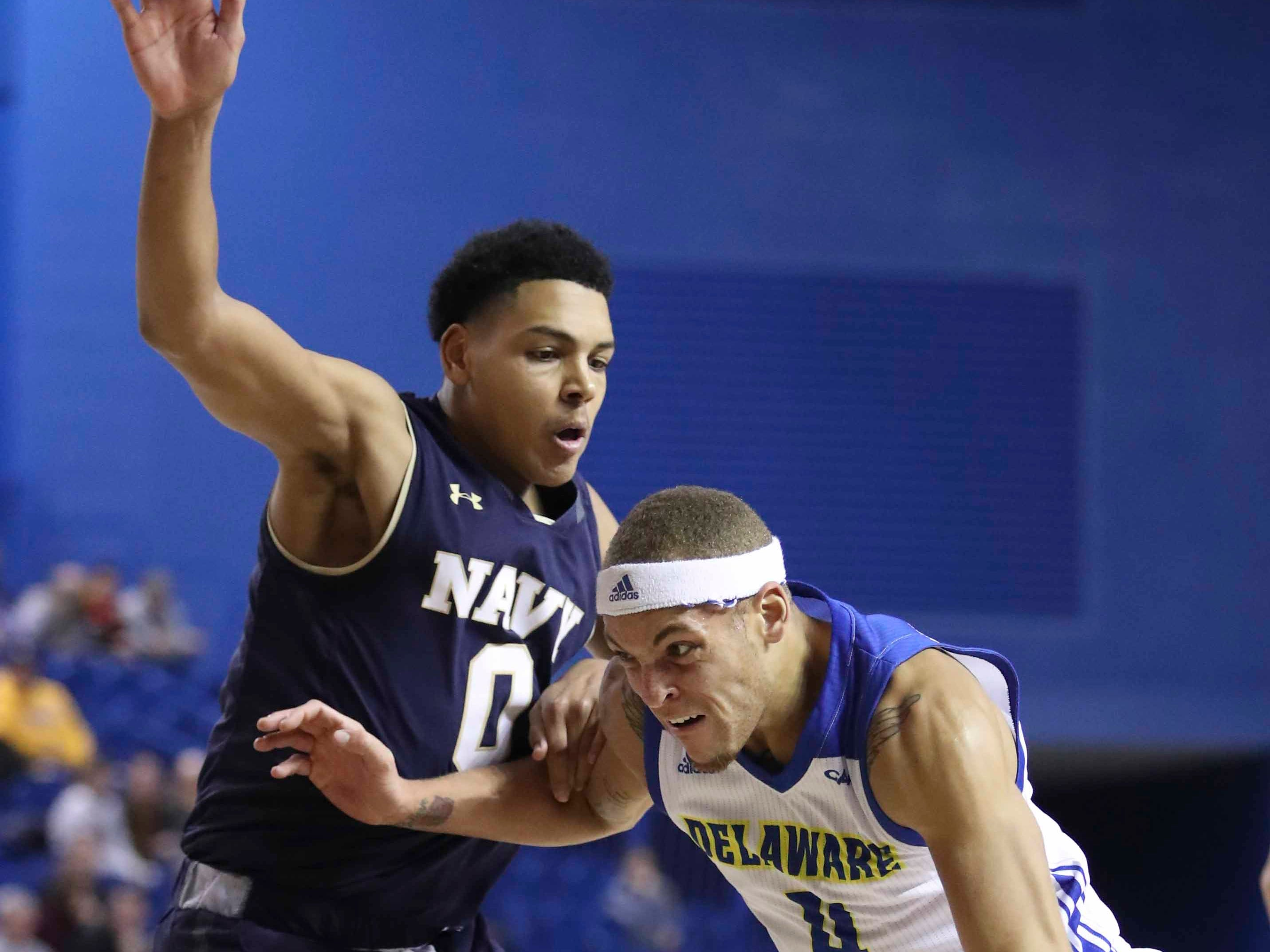 Navy's Josiah Strong (left) tries to slow Delaware's Darian Bryant in the first half at the Bob Carpenter Center Wednesday.