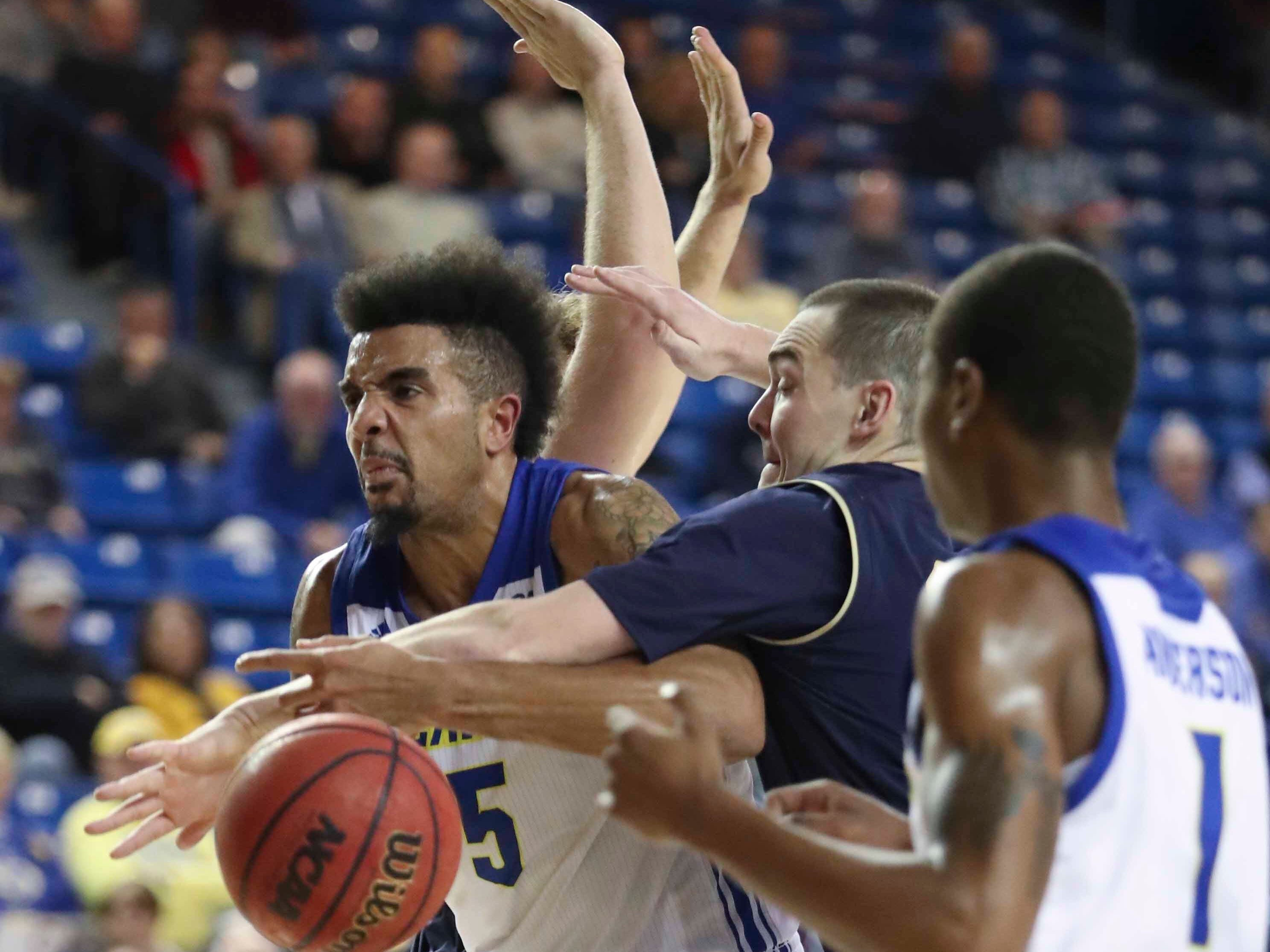 Delaware's Eric Carter (left) is fouled by Navy's George Kiernan in the second half of Delaware's 80-65 loss at the Bob Carpenter Center Wednesday.
