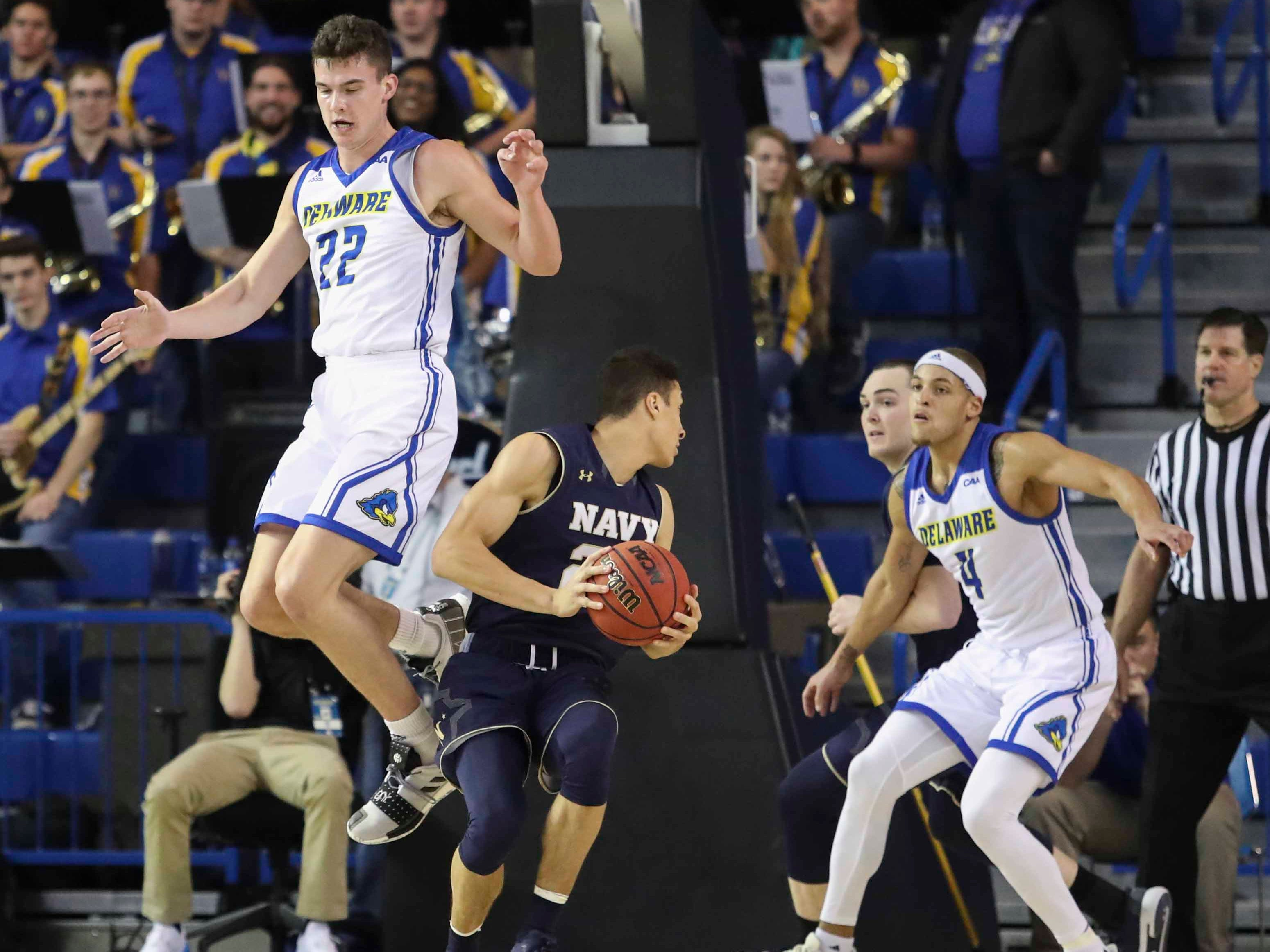 Delaware's Jacob Cushing (left) leaps the wrong way as teammate Darian Bryant joins in defense against Navy's Cam Davis in the second half of Delaware's 80-65 loss at the Bob Carpenter Center Wednesday.